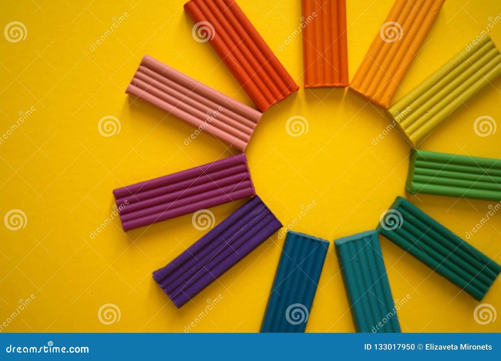 Части пестротканого пластилина для детей против желтой предпосылки