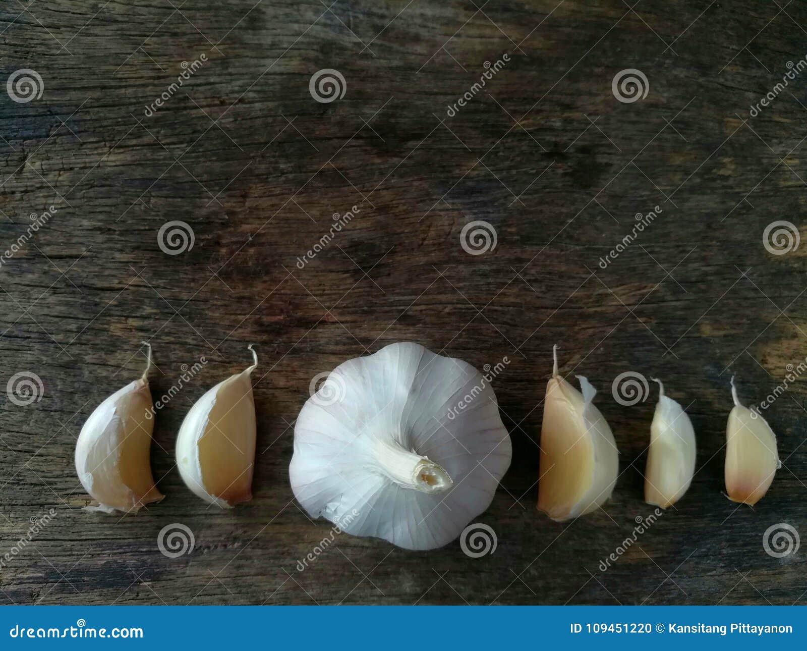 Части чеснока, аранжируют линию, деревянную предпосылку