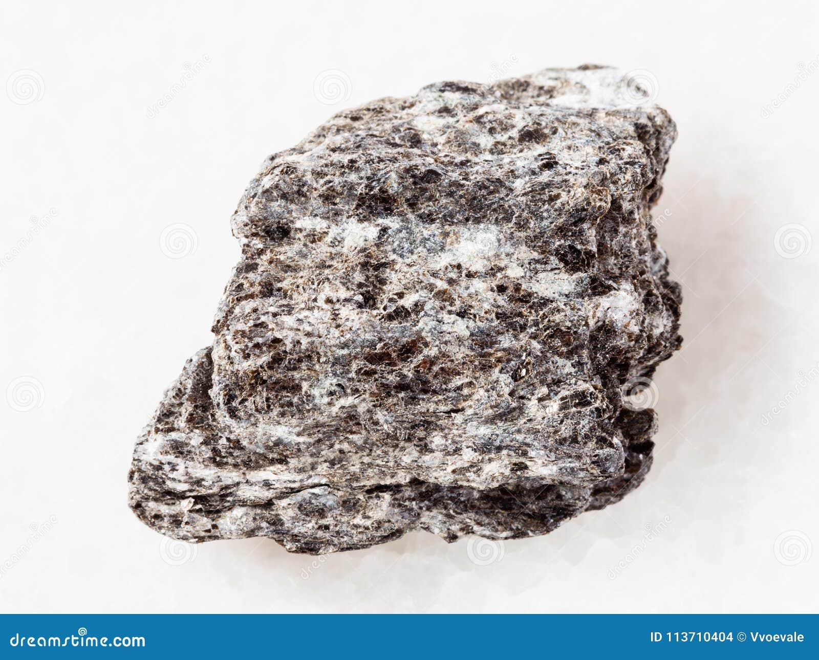 часть камня сланца кварц-биотита на белизне