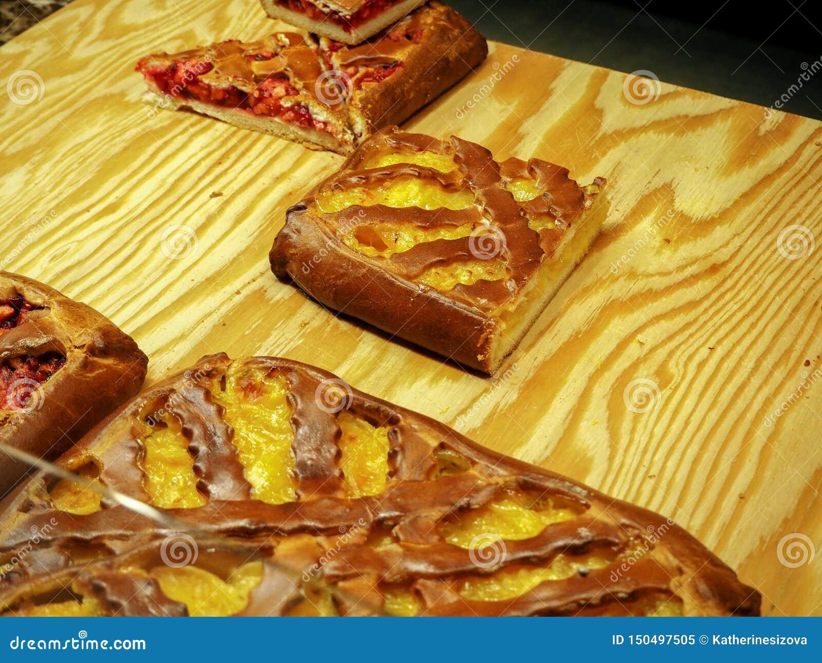Часть пирога плода с желтым цветом и красной завалки на деревянной доске