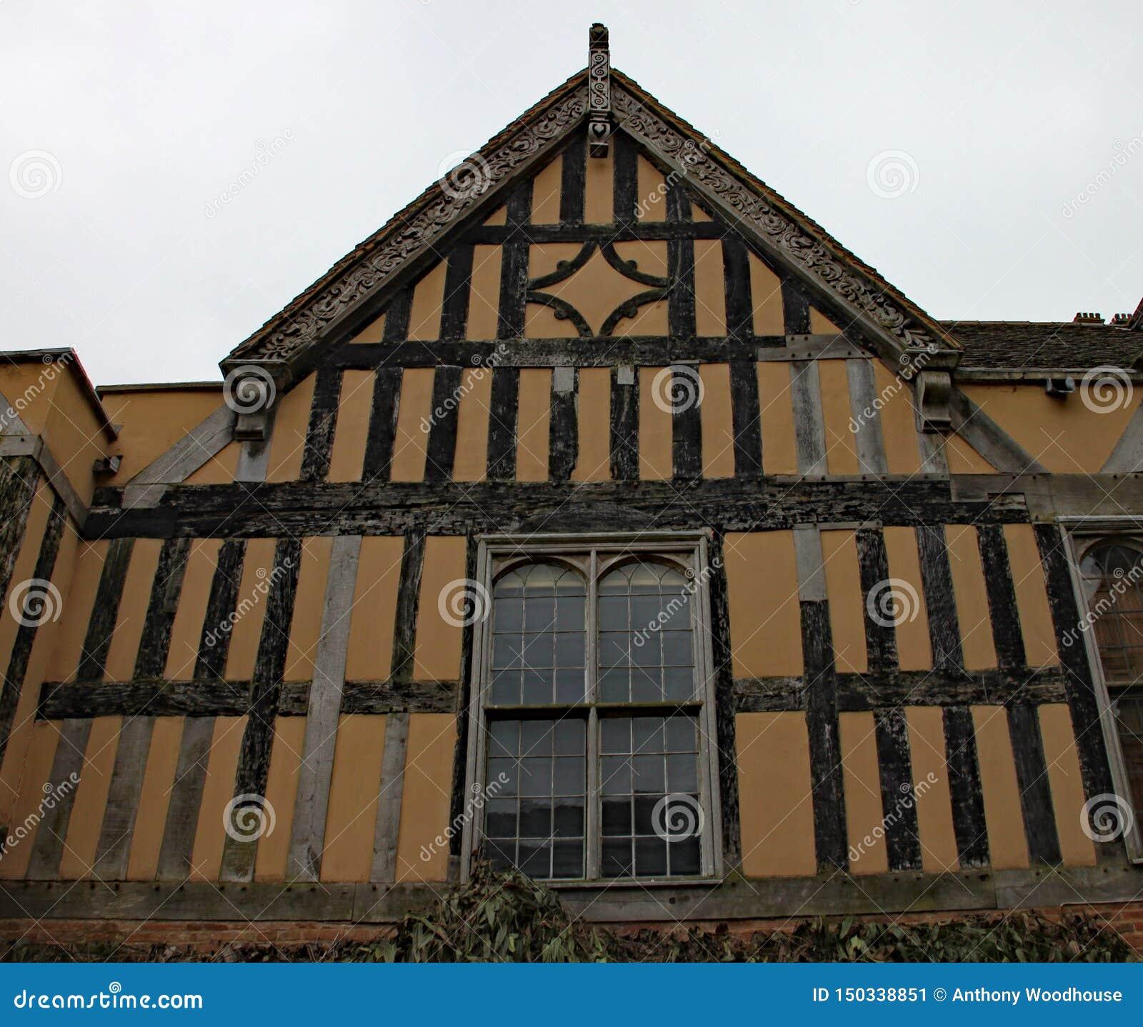 Часть половинного тимберса обрамила здание с богато украшенным резным изображением на досках facia