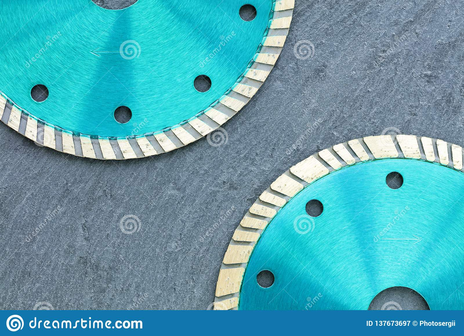 Часть режущих дисков диаманта изумрудного цвета на фоне серого гранита
