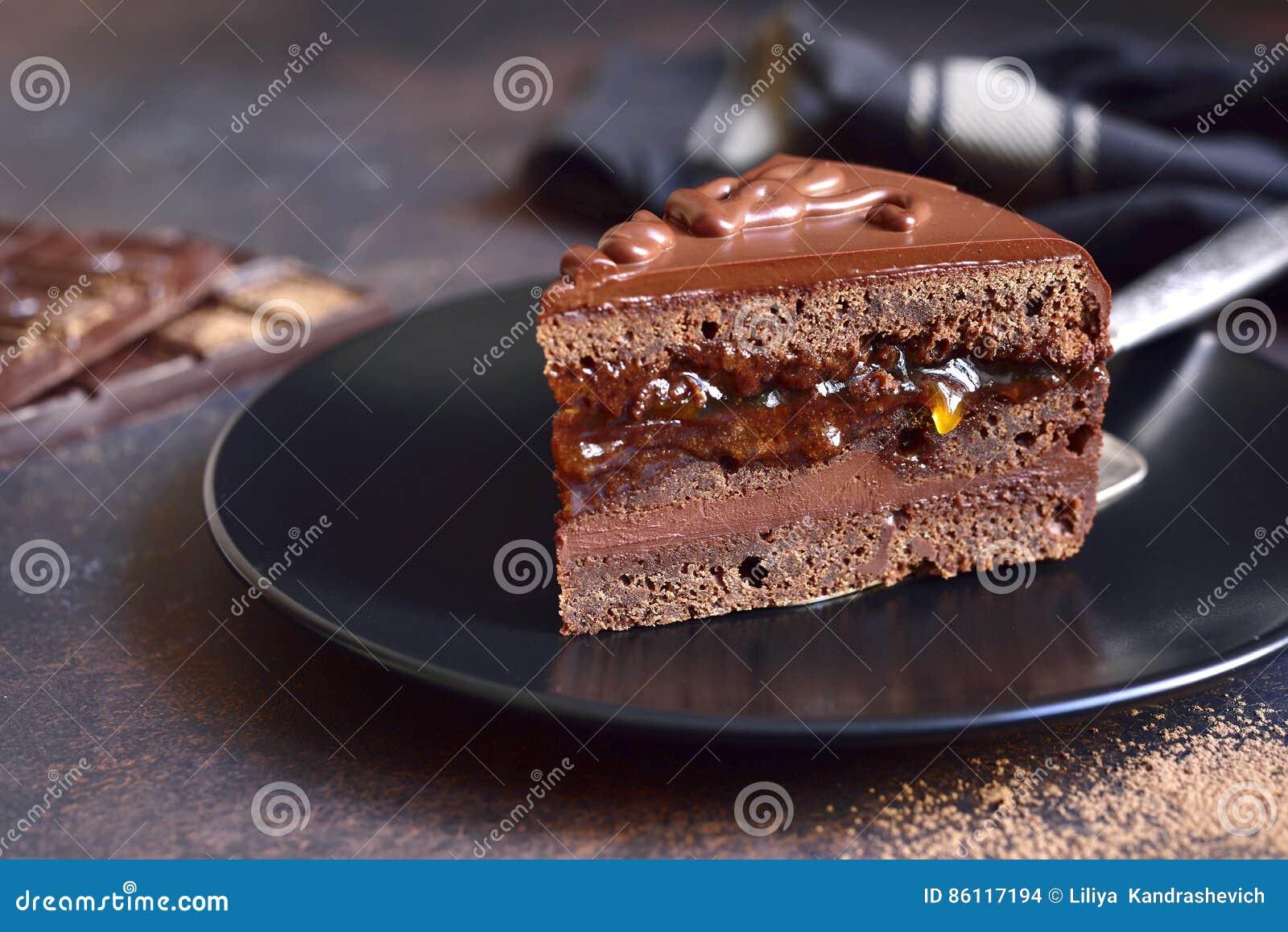 Часть torte Sacher шоколада на черной плите на шифере, ston