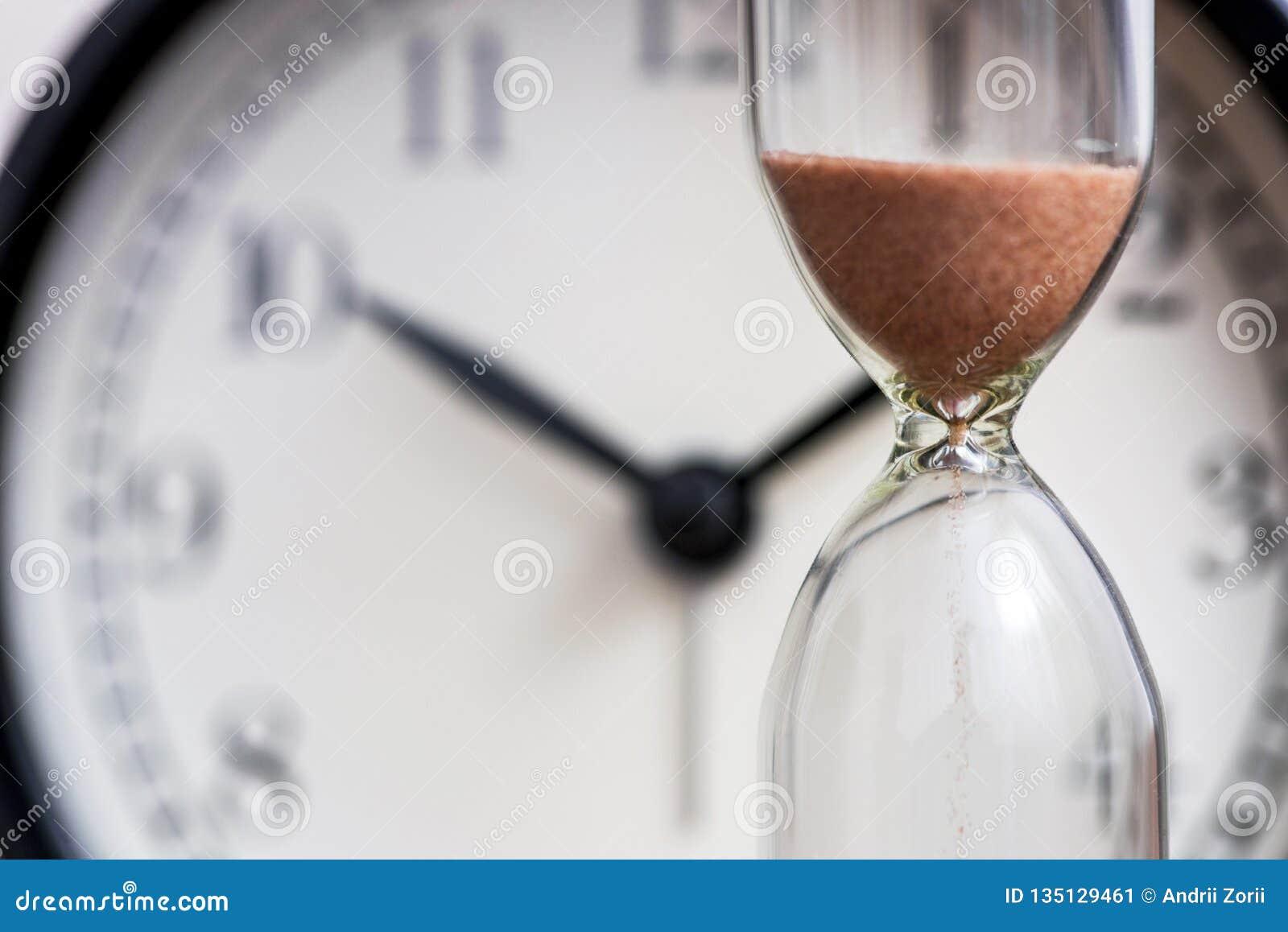 Часы на предпосылке дозора офиса как время проходя концепцию для крайнего срока, срочности и хода дела из времени песок