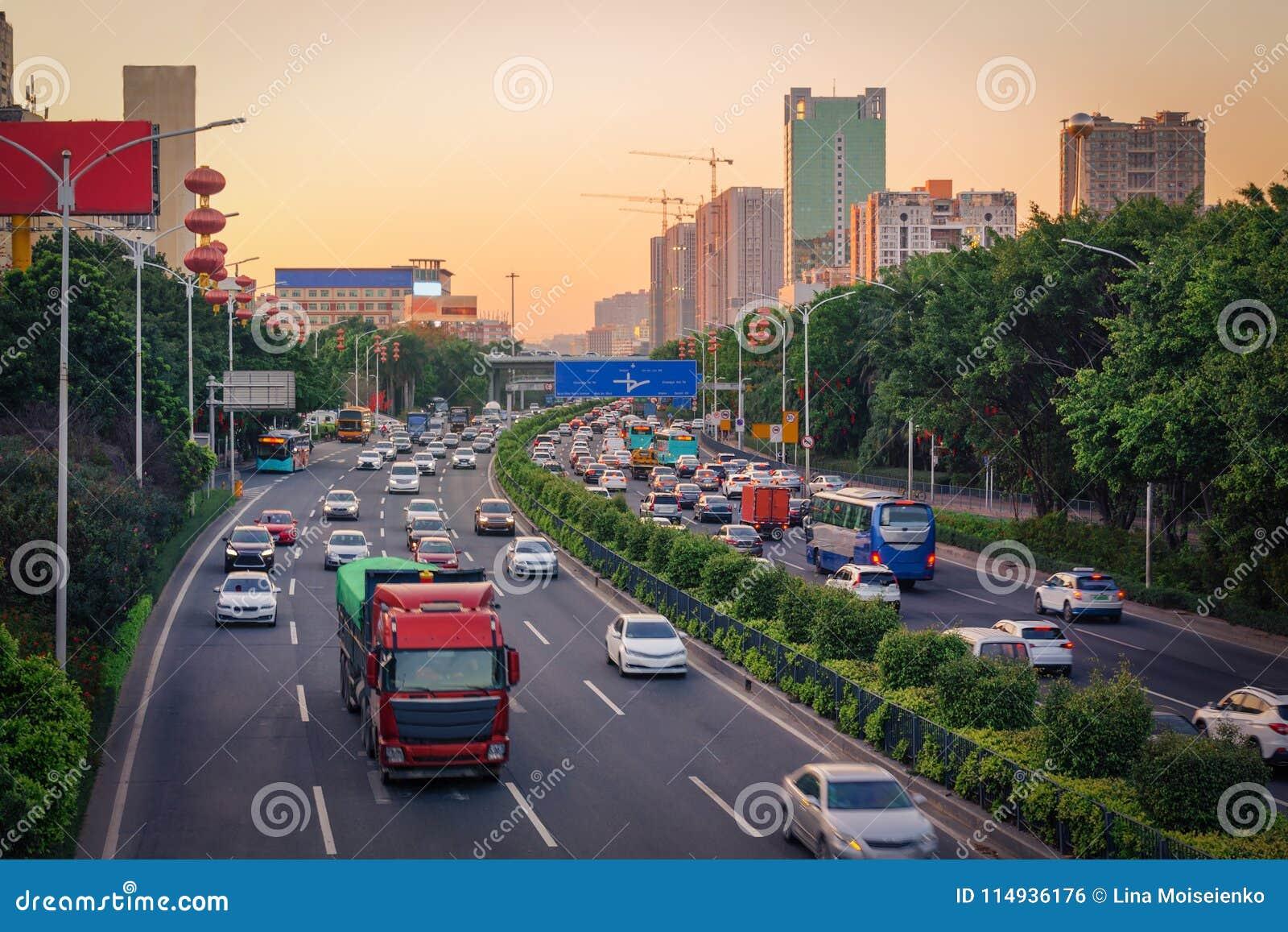 Час пик вечера в большом городе, заторе движения от много автомобилей на дороге разделенного шоссе, занятом городском взгляде на