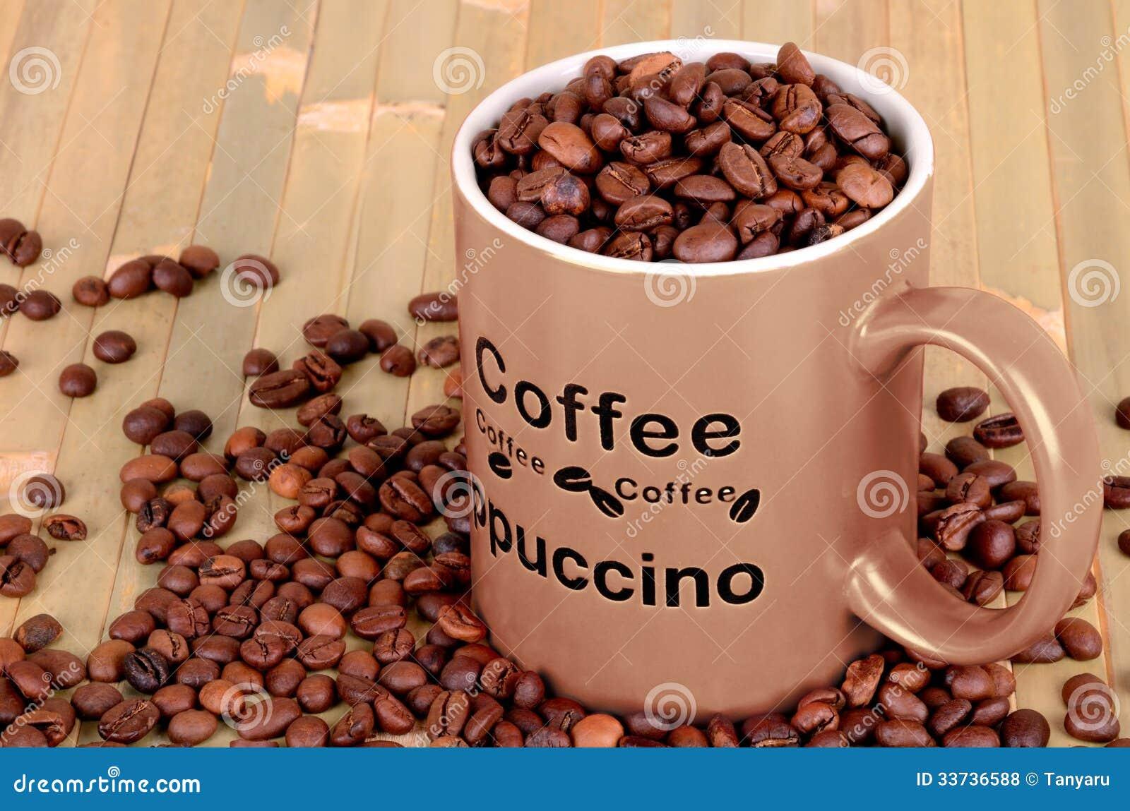 Чашка Брайна с кофейными зернами на деревянной таблице