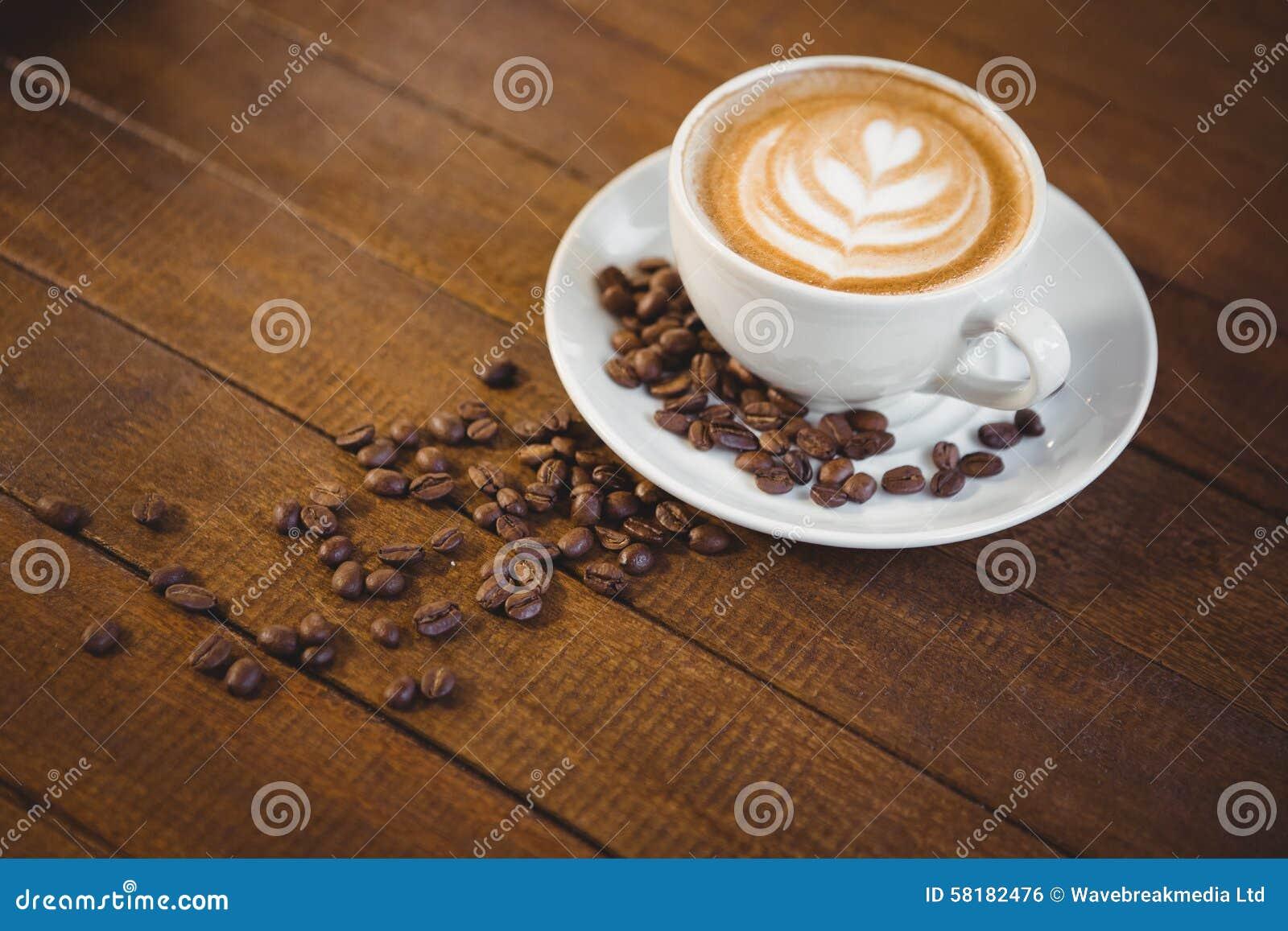 Чашка капучино с искусством кофе и кофейными зернами