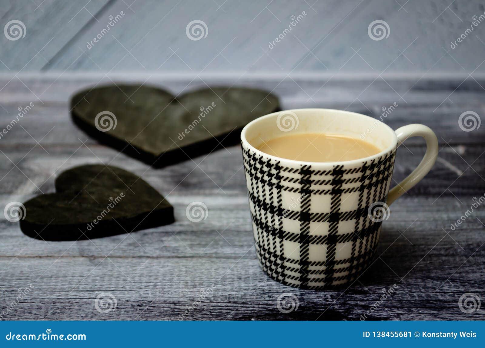 Чашка кофе на деревянном столе с 2 темными деревянными винтажными сердцами