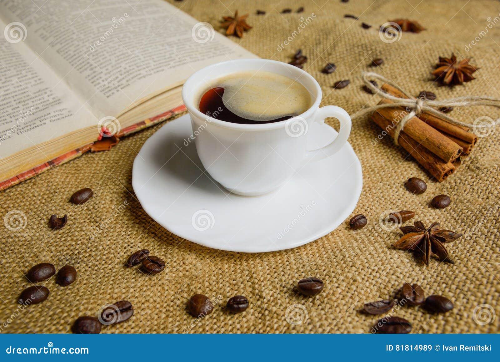 Чашка кофе на предпосылке мешковины с книгой макрос кофе завтрака фасолей идеально изолированный над белизной одушевляя