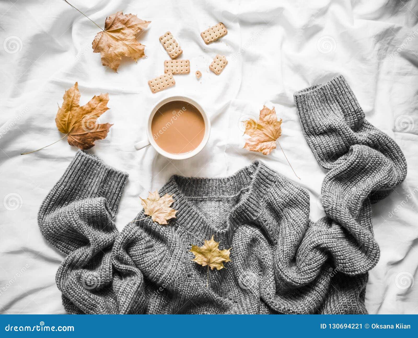 Чашка кофе, серая греет связанный свитер сверхразмерный, листья желтого цвета сухие на кровати - уютном домашнем натюрморте, взгл