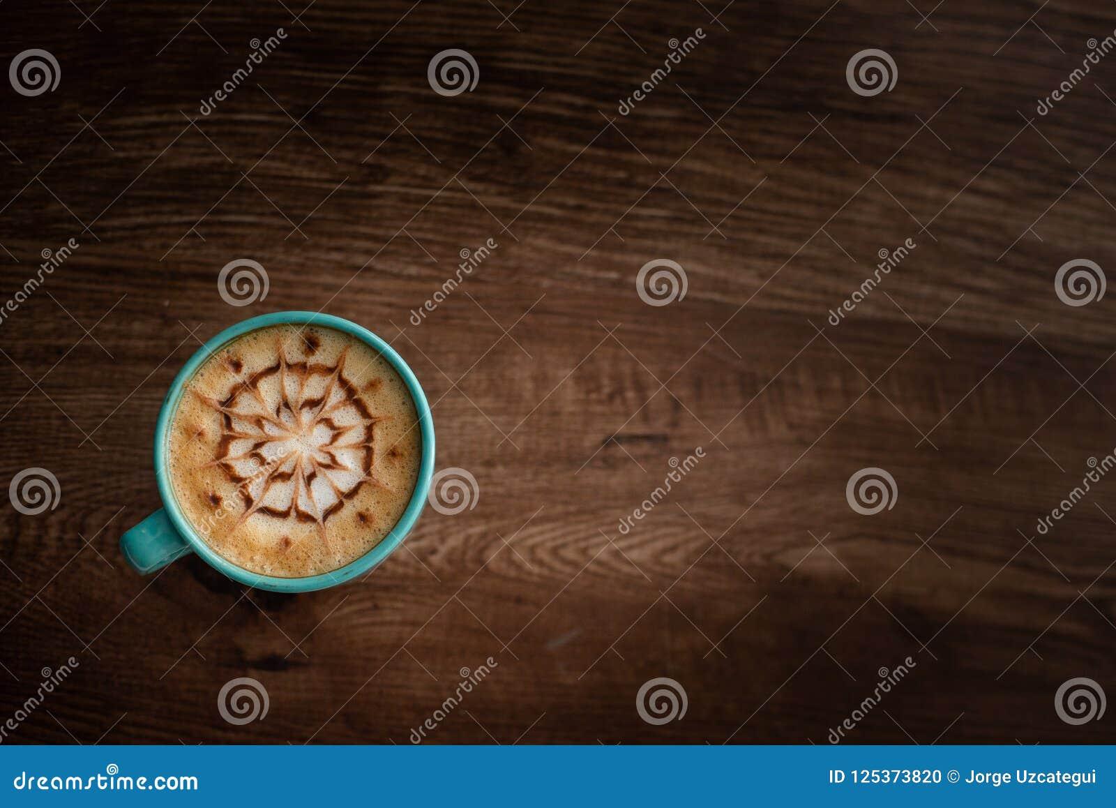 Чашка кофе с дизайном искусства на своей верхней части