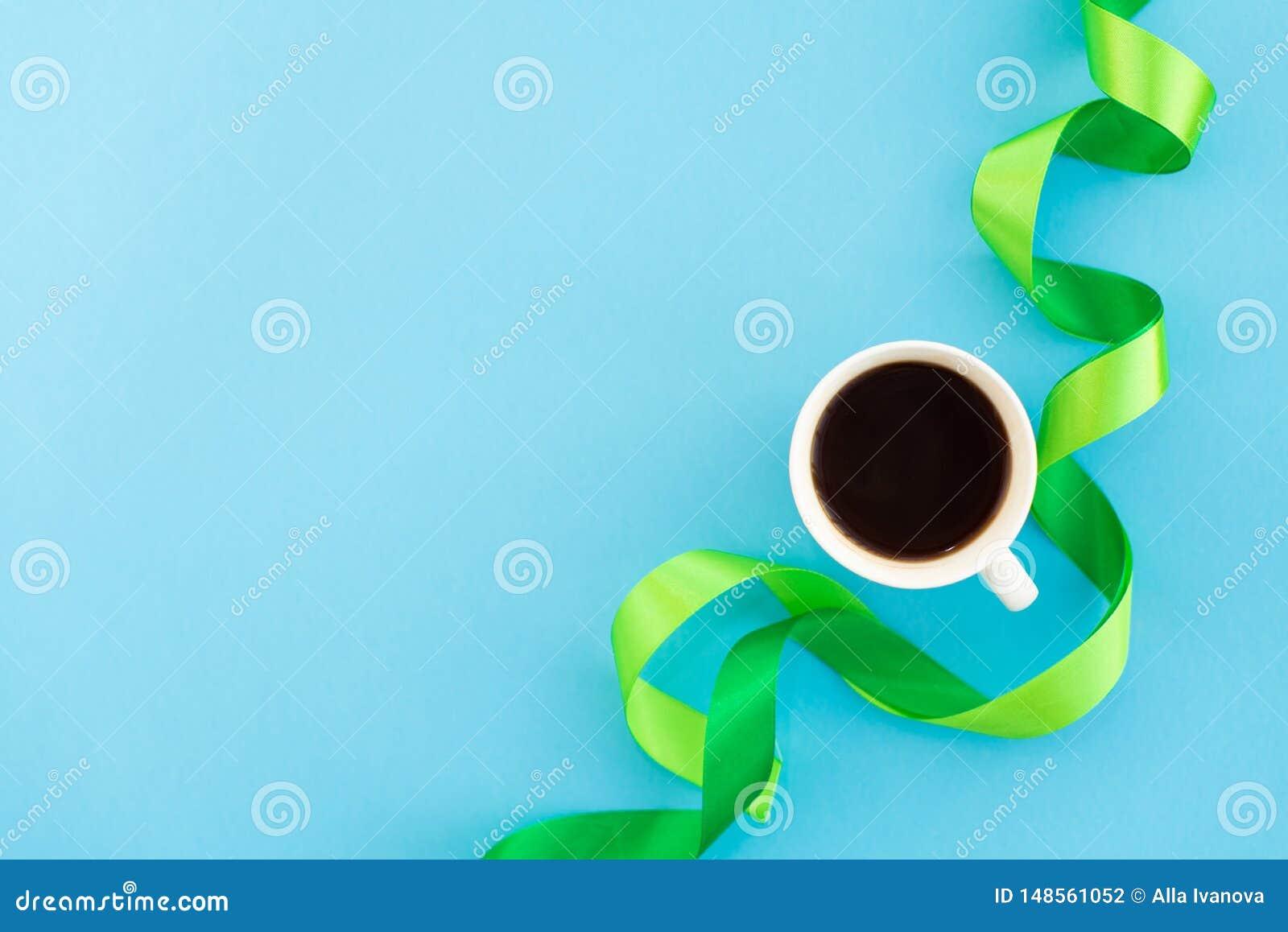 Чашка кофе с зелеными лентами шелка на голубой предпосылке Концепция дизайна минимальная Mocup