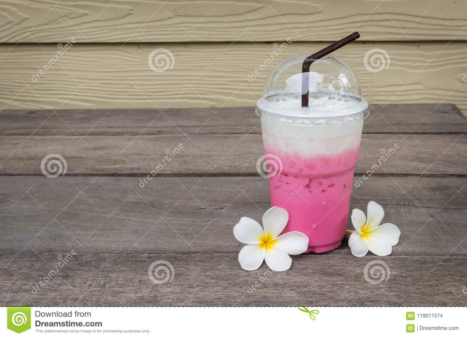 Чашка розового молока льда около Plumeria цветет на деревянном поле