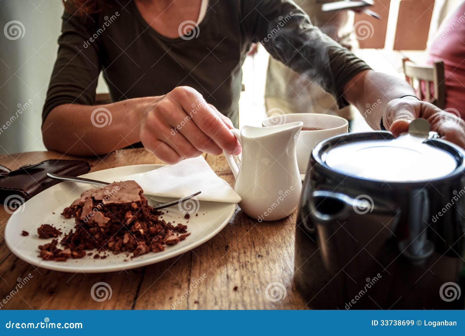Чашка чаю молодой женщины лить и торт еды в кафе