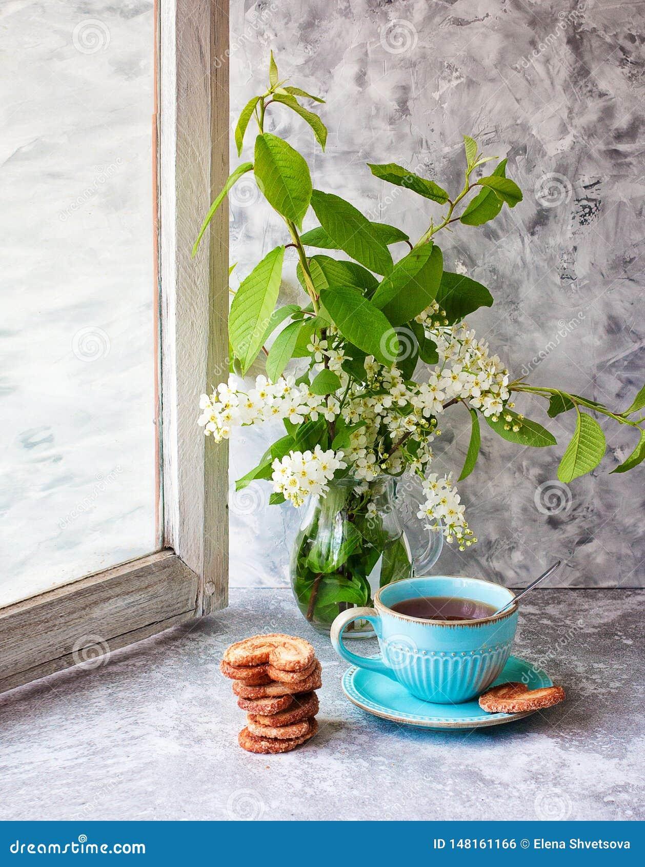 Чашка чаю, печенья, букет вишни птицы в стеклянной вазе на серой таблице Печенья Берлина r Выпивать чая r