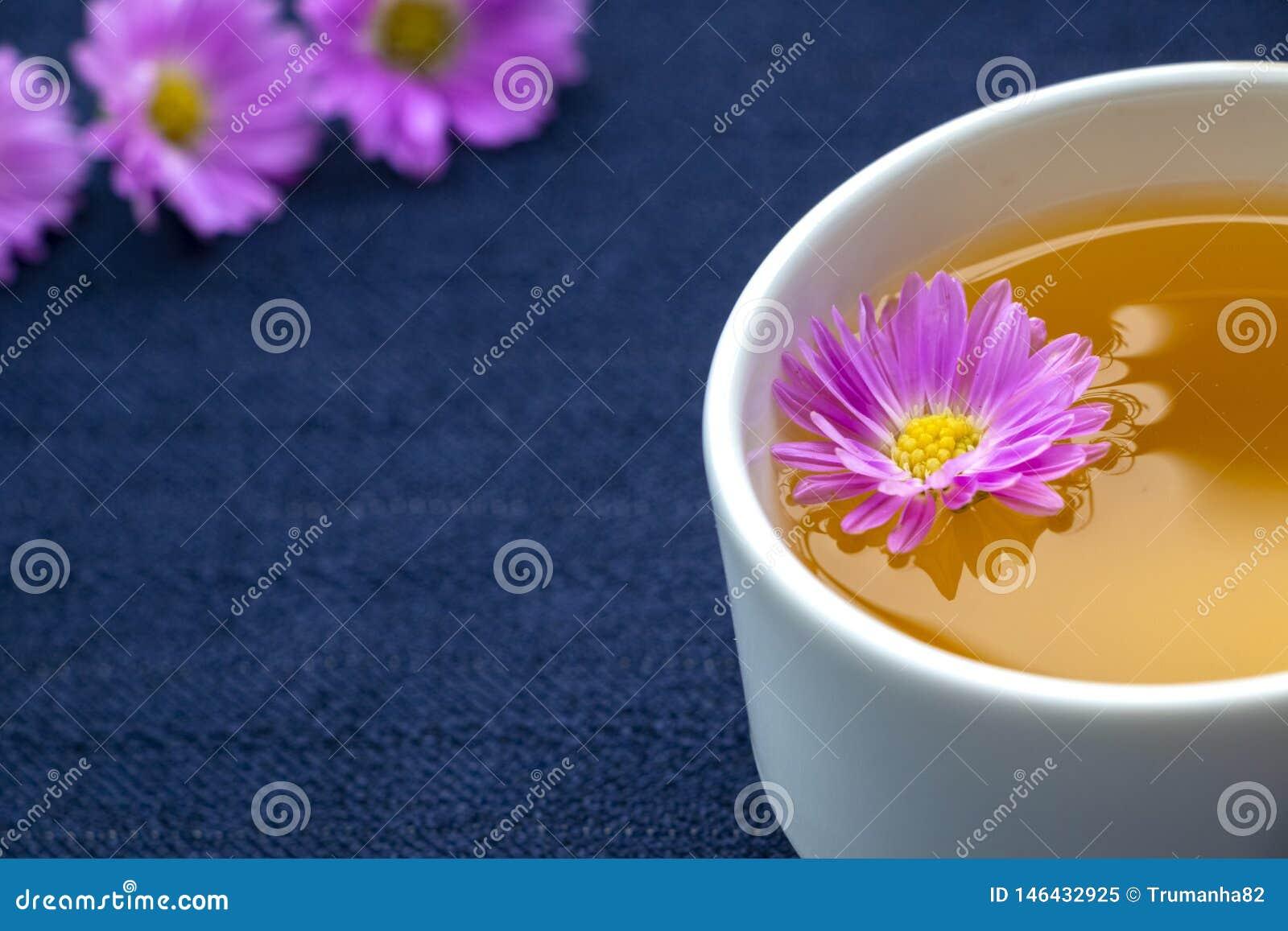 Чашка чая и фиолетовые цветки на темно-синей предпосылке скатерти