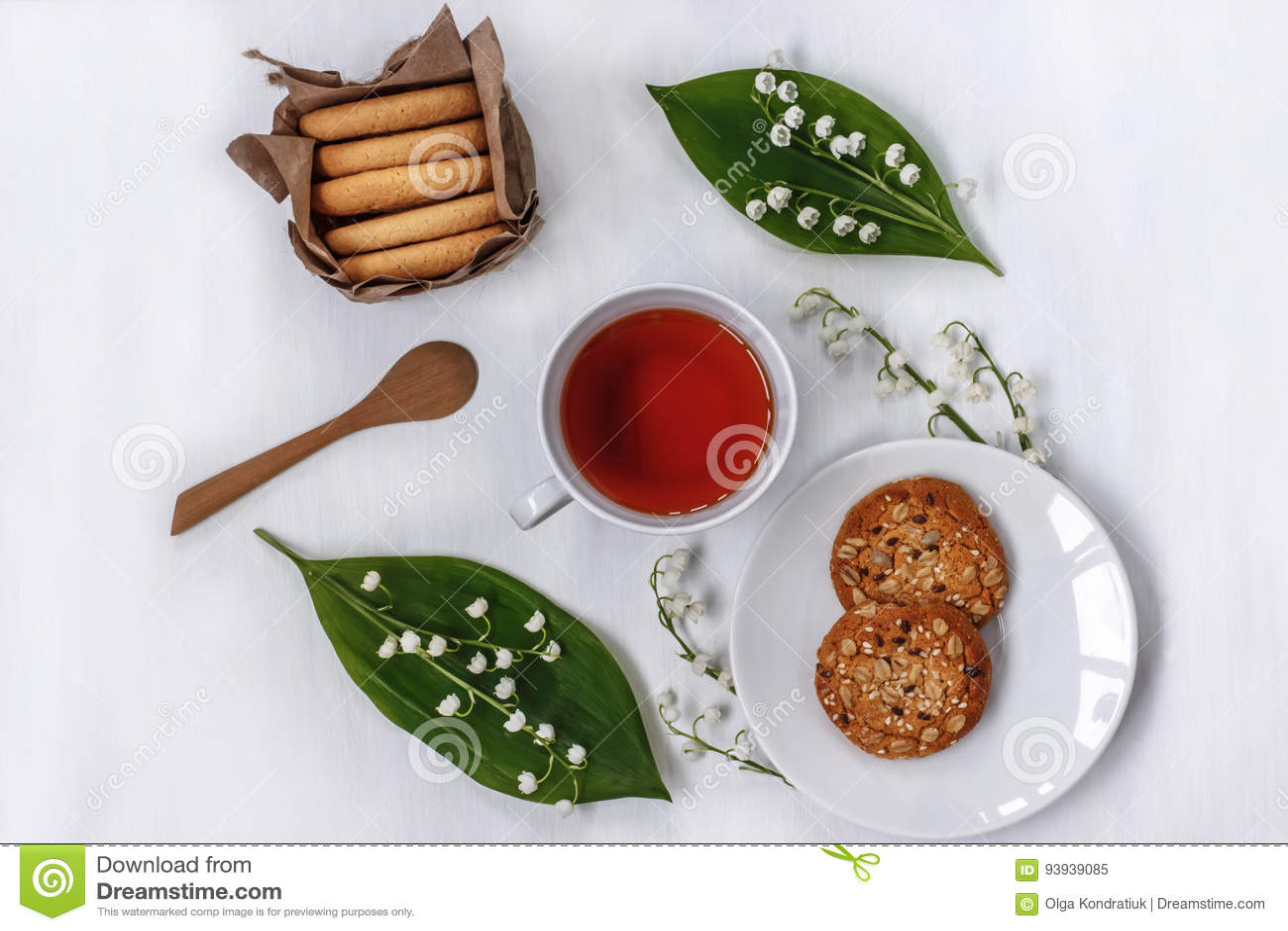 Чашка черного чая в круге цветков печений ландыша, овса и миндалины на белой предпосылке