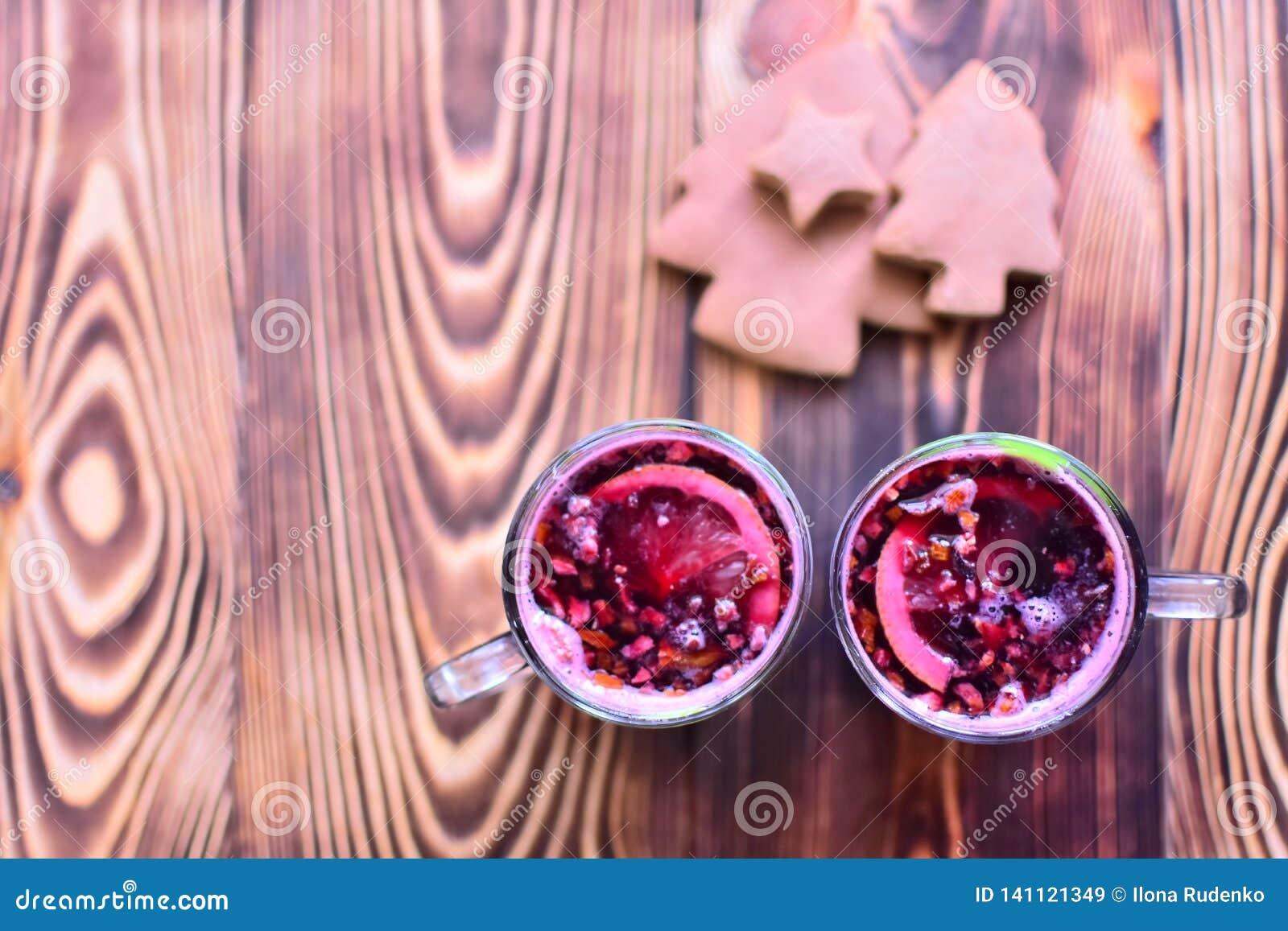 2 чашки красной обдумыванной лозы со специями, цитрусовыми фруктами и вкусными пряниками лежа на темном деревянном столе Взгляд с