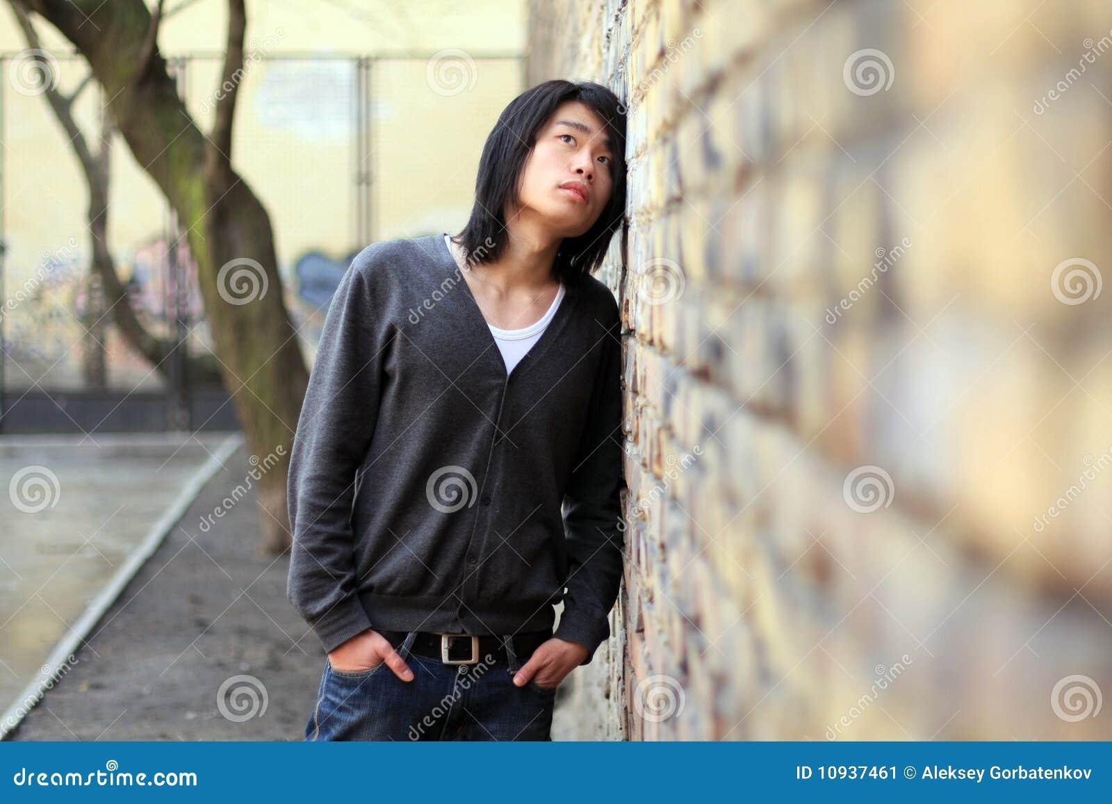 человек азиатской осени сухопарый смотря вверх по стене