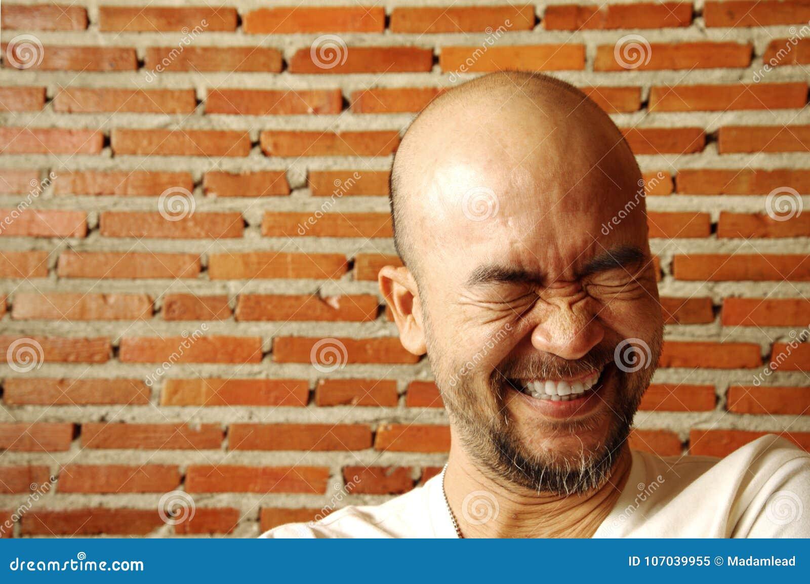 Человек азиатской японской бороды портрета облыселый смеясь над с кирпичной стеной