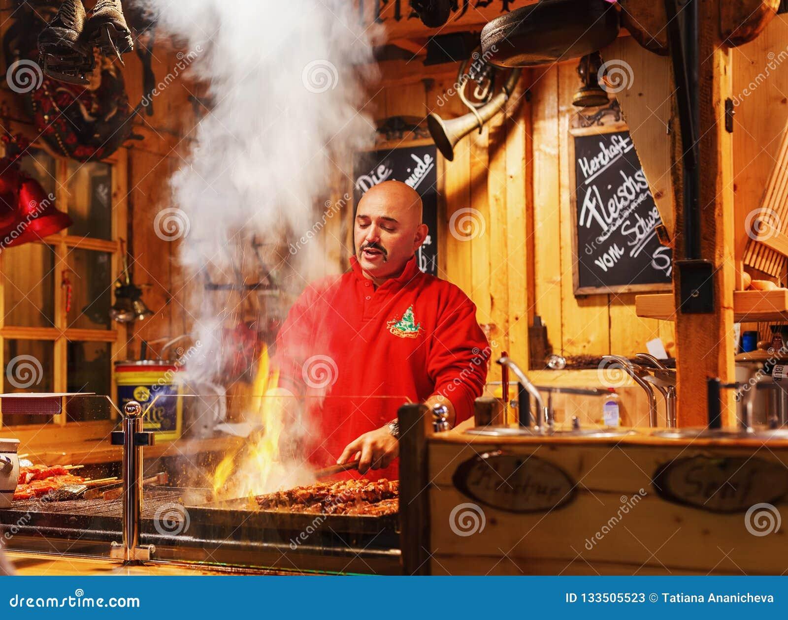 Человек варя kebab на ярмарке рождества в вечере