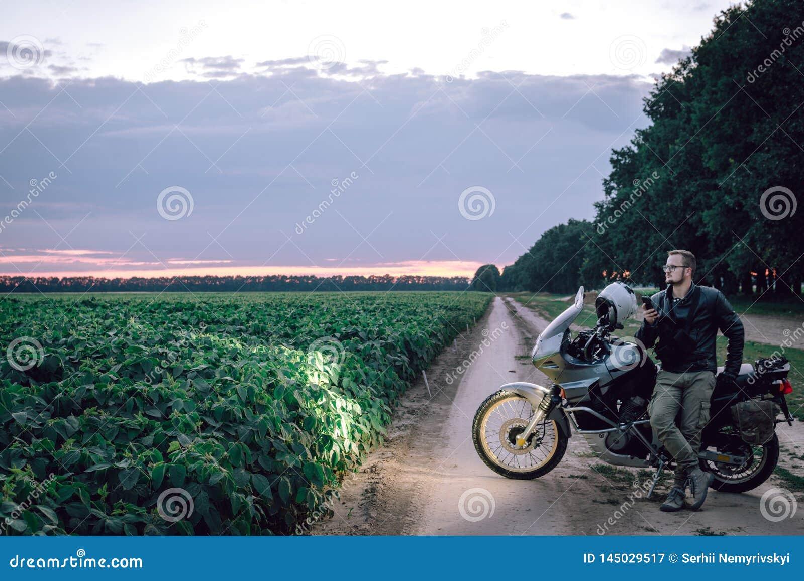 Человек велосипедиста в кожаной куртке стоя на открытом воздухе с его