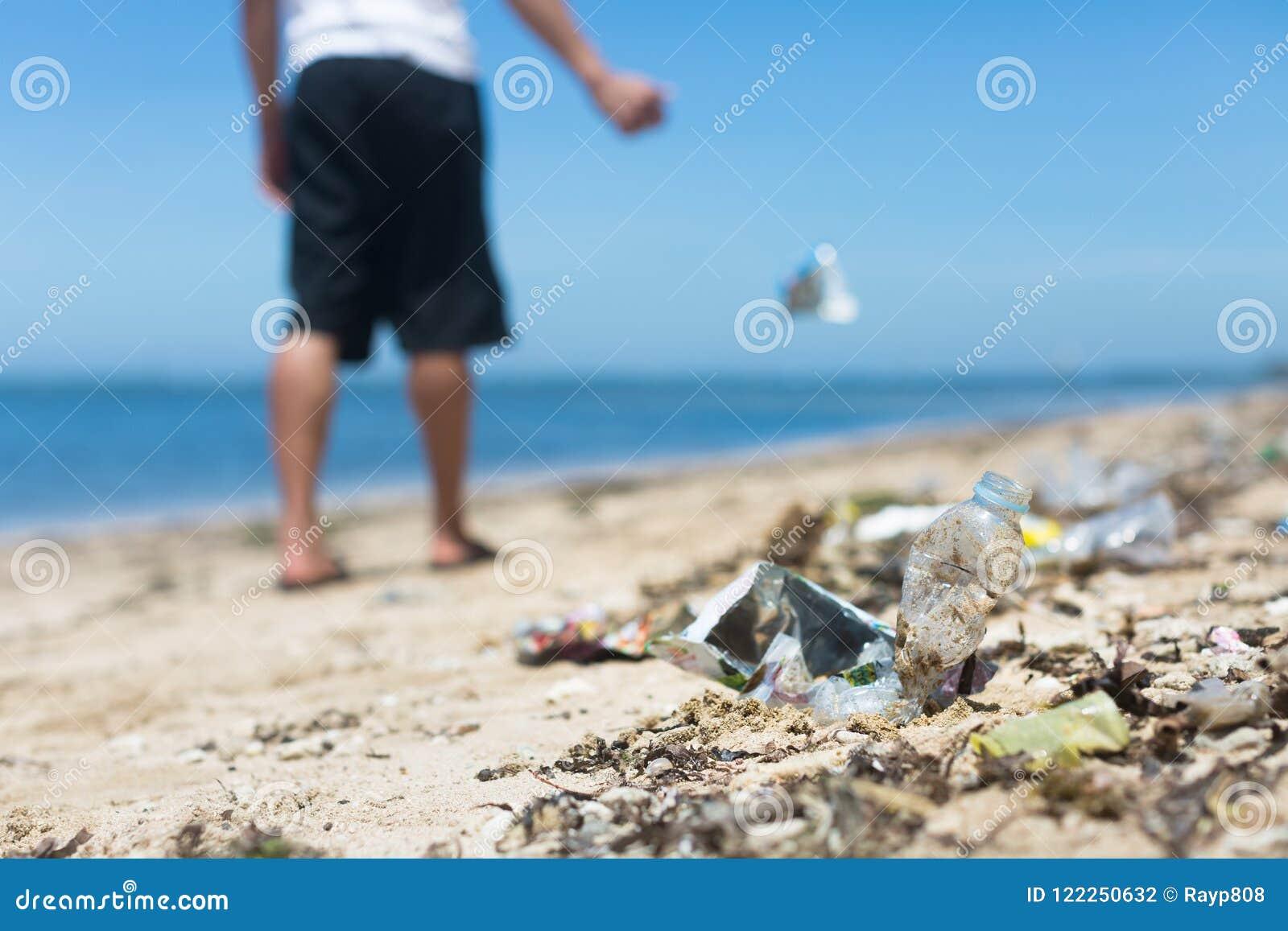 Человек вскользь бросает отброс на том основании, добавляющ к большое количество сора на пляже