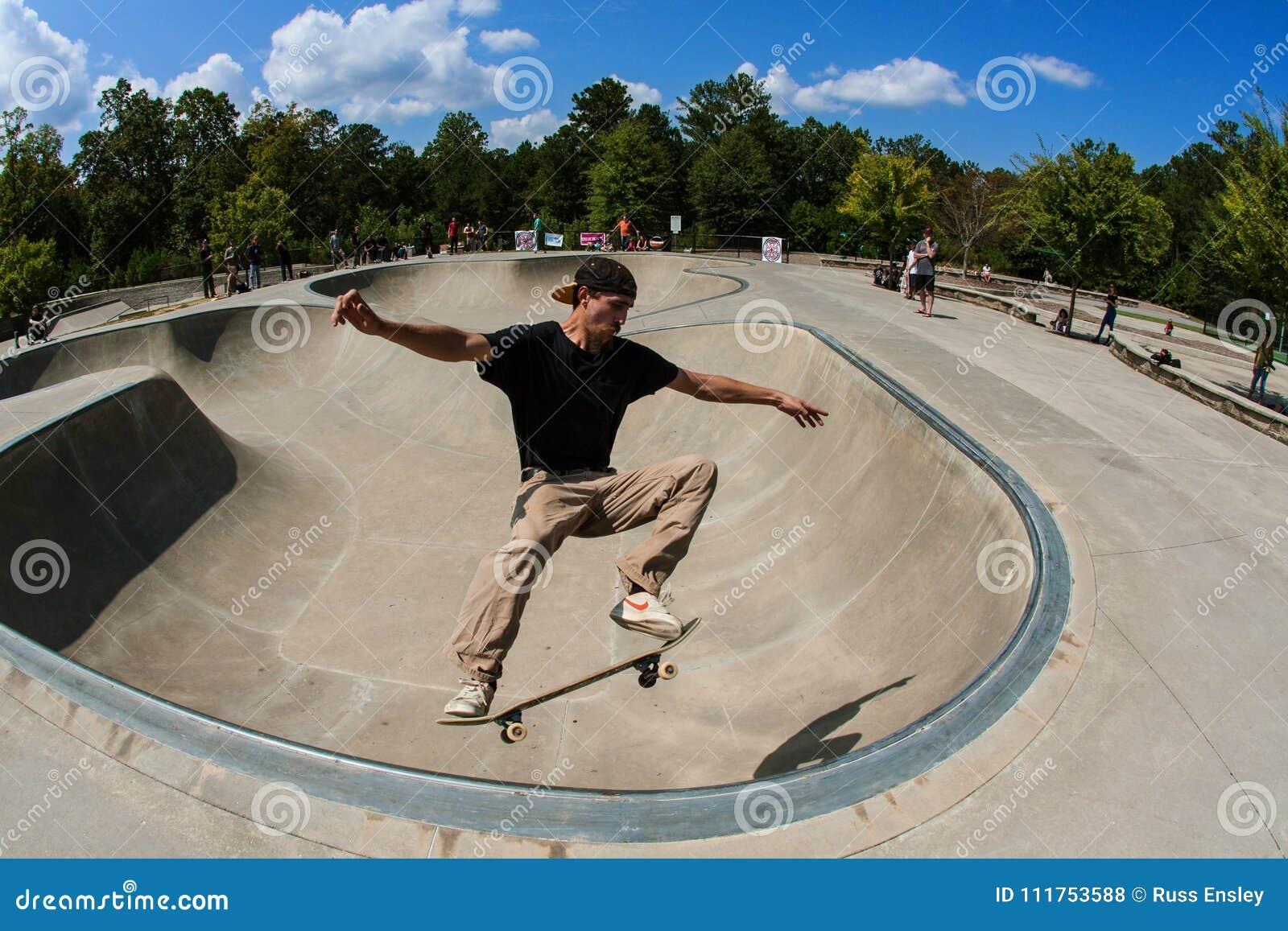 Человек выполняет фокус Midair в шаре на парке скейтборда