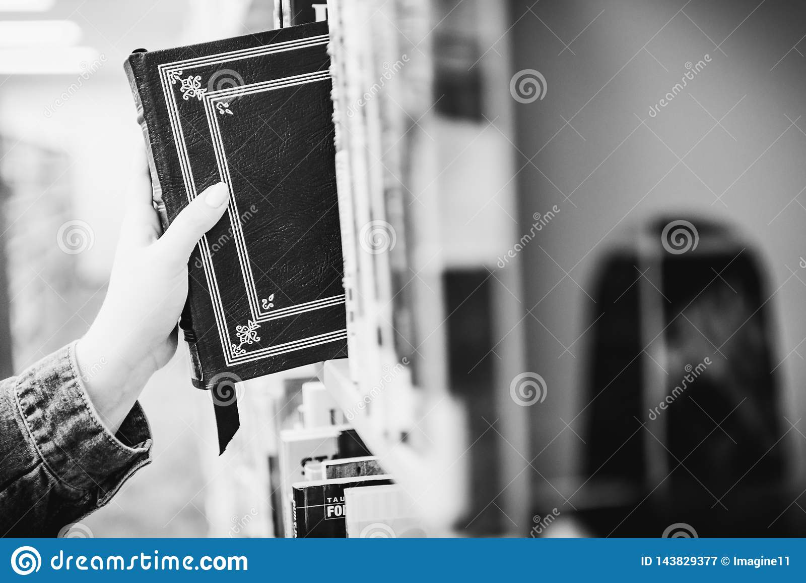Человек вытягивая книгу от полки библиотеки