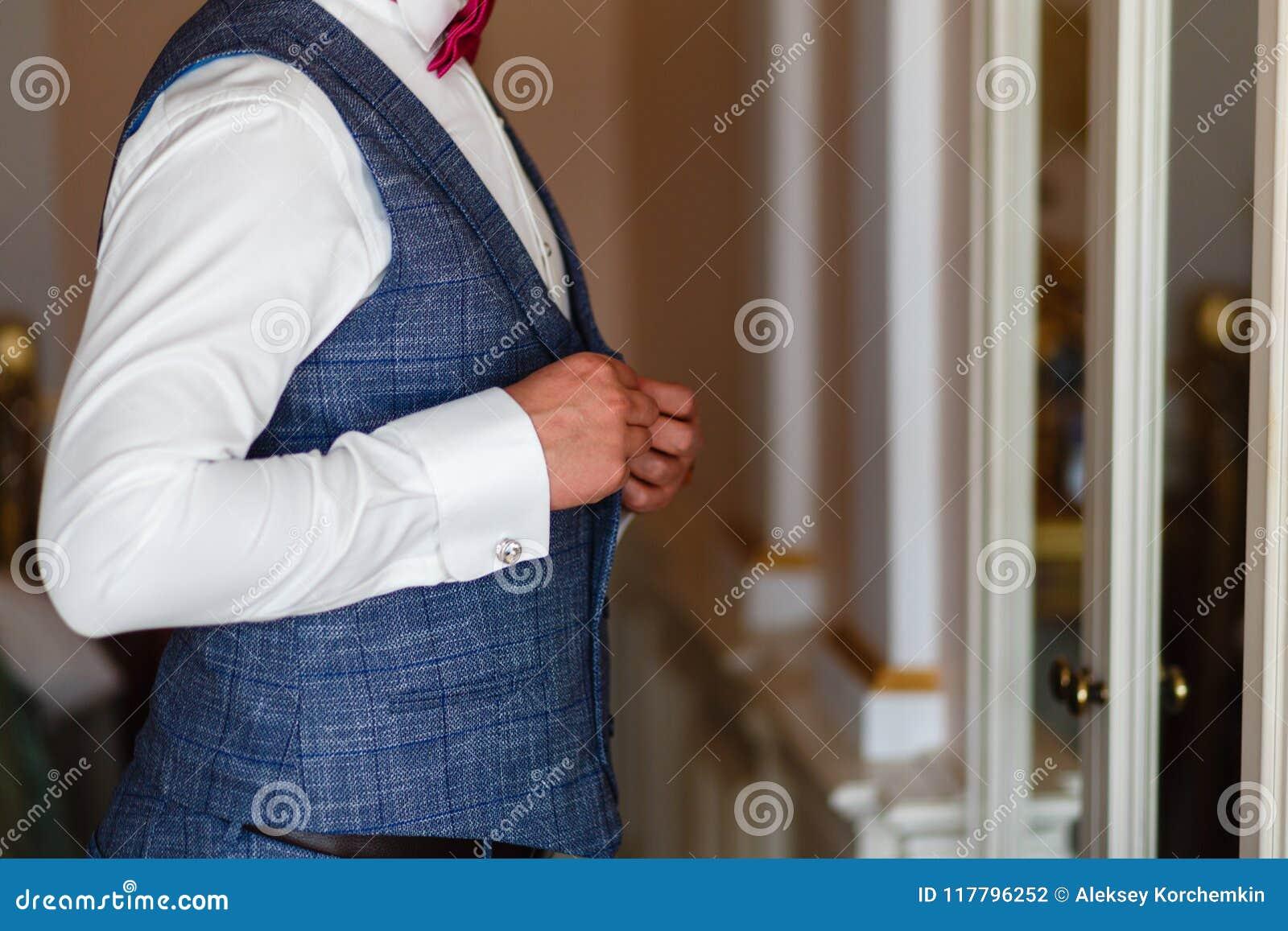 Человек в белой рубашке и сером жилете прикрепляет кнопки перед зеркалом Groom в сером костюме и связь получая готовый в morni