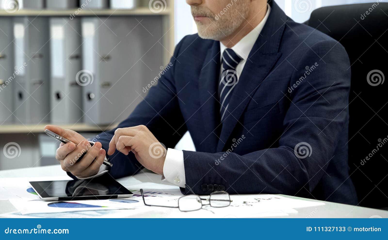 Человек в деловом костюме проверяя электронную почту на smartphone в офисе, современной технологии