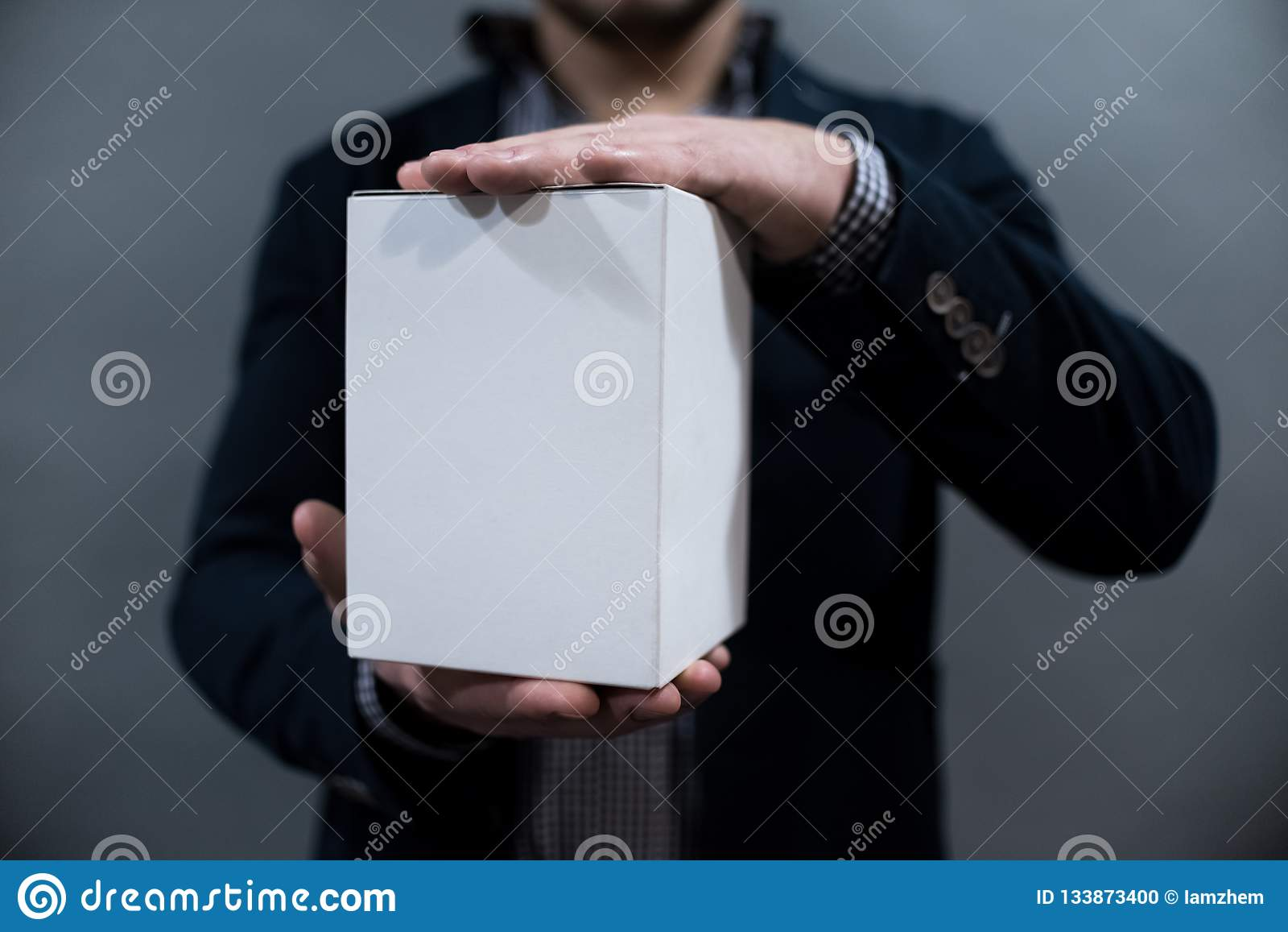 Человек в куртке и рубашке держа коробку белой бумаги