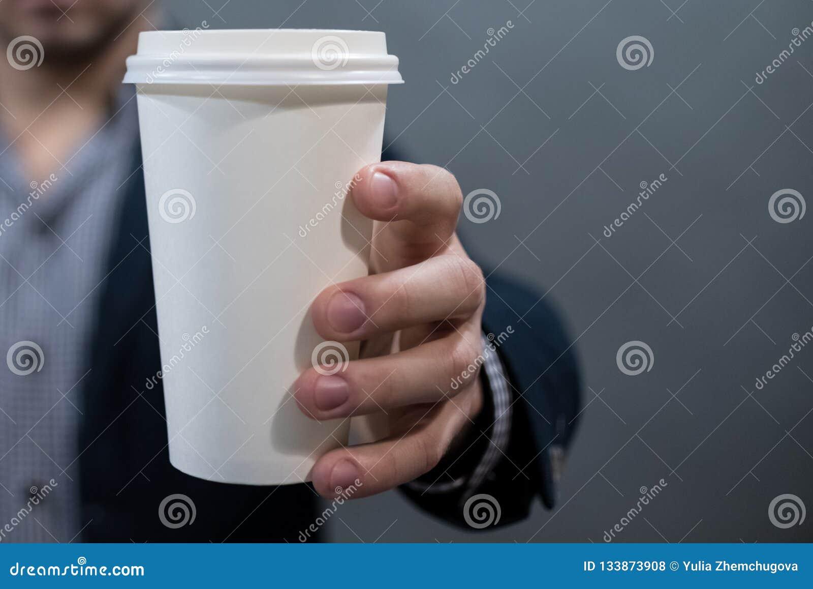 Человек в куртке и рубашке держа чашку белой бумаги пустая белизна для вашего текста