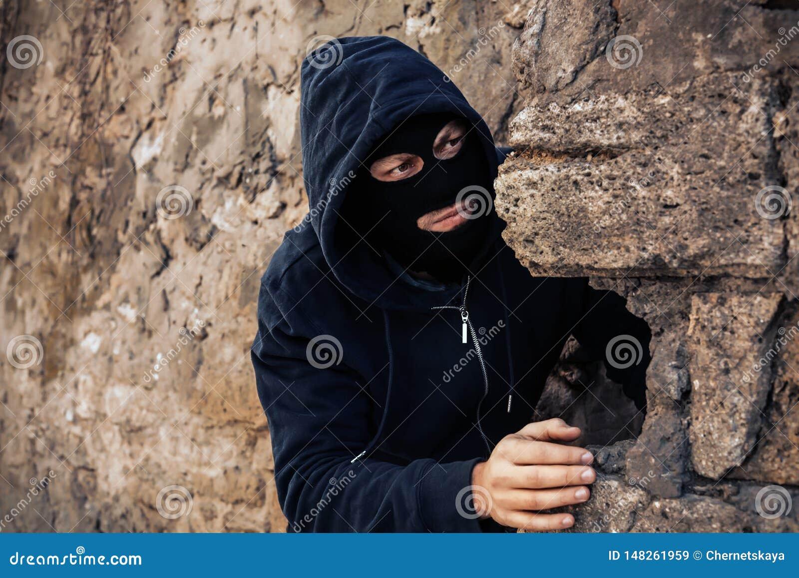 Человек в маске за каменной стеной наблюдая кто-то Преступная деятельность