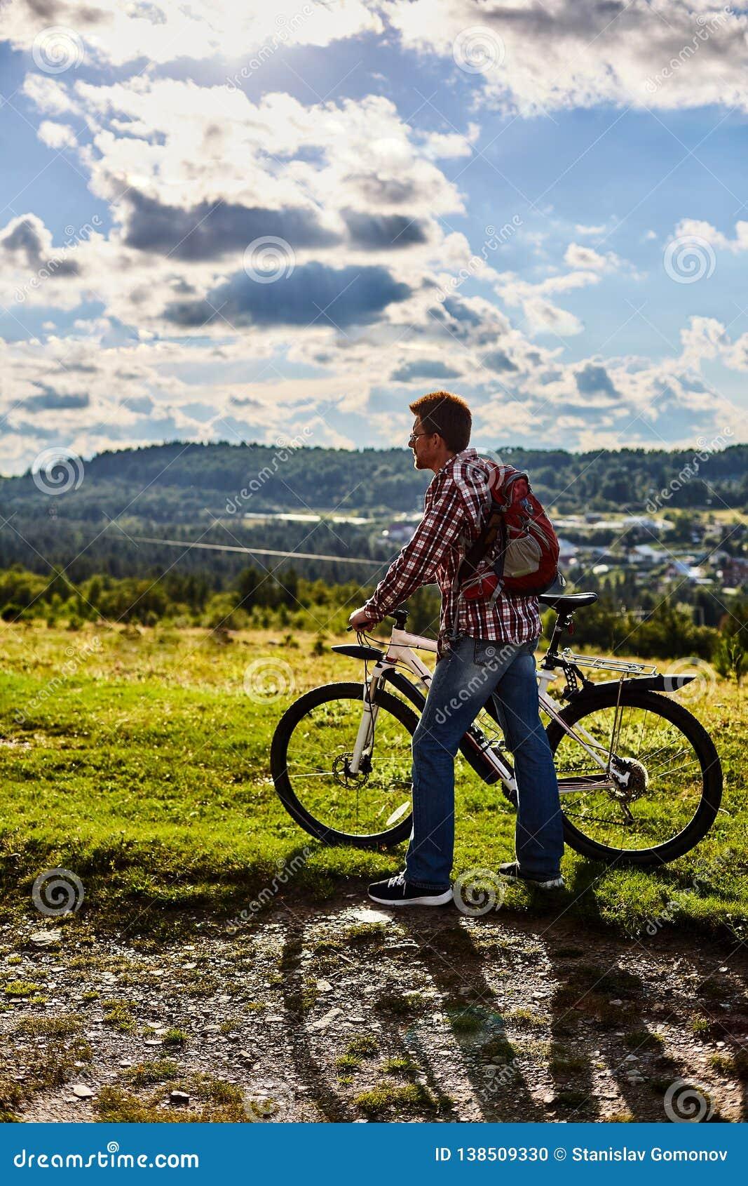Человек в природе с велосипедом на предпосылке гор и голубого неба