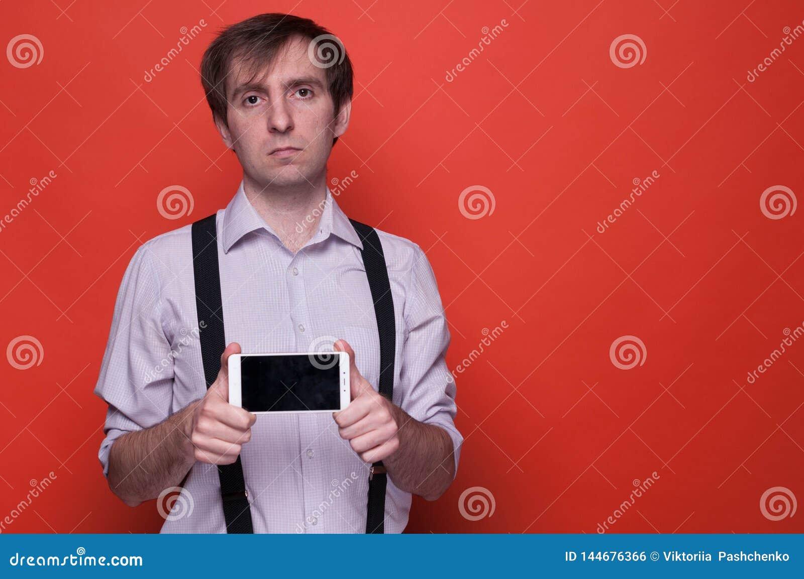 Человек в рубашке и подтяжк держа и показывая смартфон