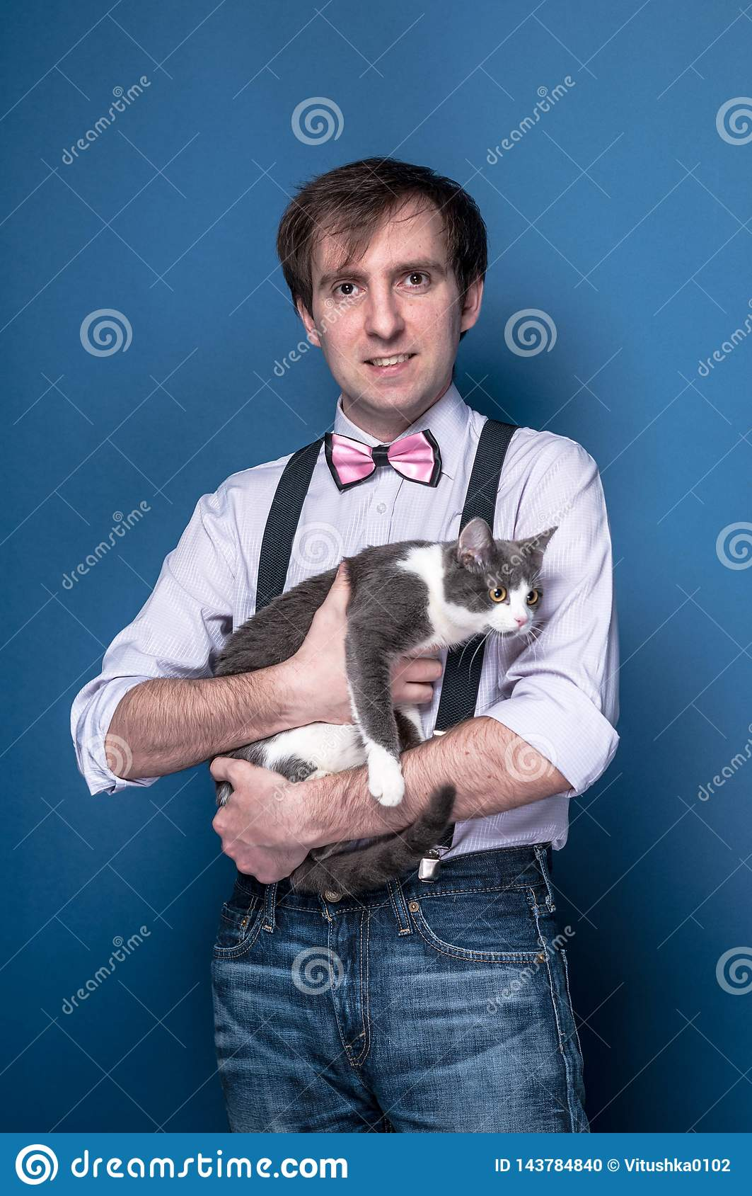 человек в рубашке, подтяжк и розовой бабочке смотря камеру, усмехаясь и держа милого серого кота