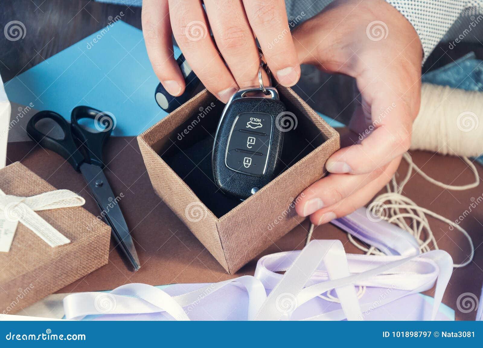 Человек в светлой рубашке подготавливает подарочную коробку на праздник тонизировать Автомобиль как подарок Ключи автомобиля в по