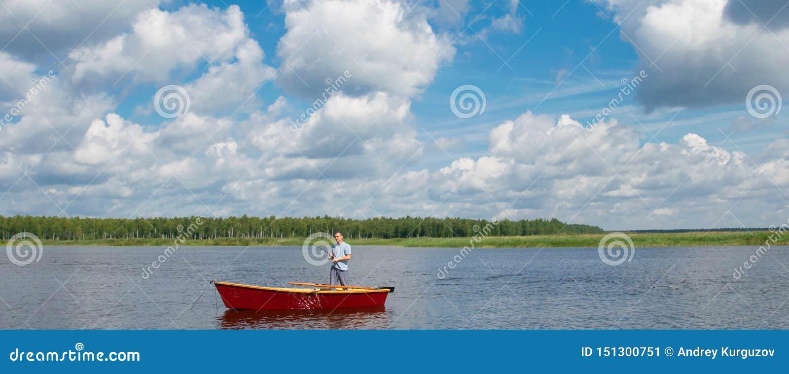 Человек в шлюпке, в центре озера, держит удя поляка для того чтобы уловить большую рыбу, против красивого неба