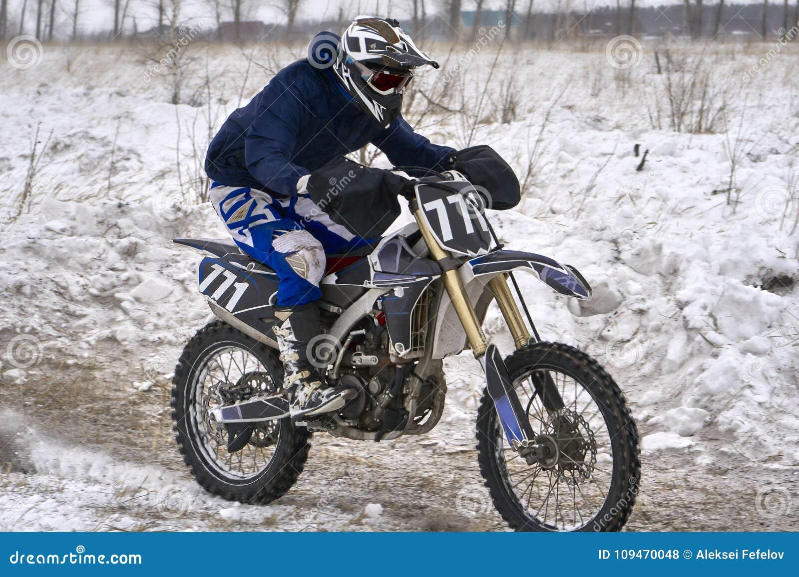 Человек гонщика спортсмена выполняет быструю езду на мотоцикле на крайности дороги Трасса очень неровна