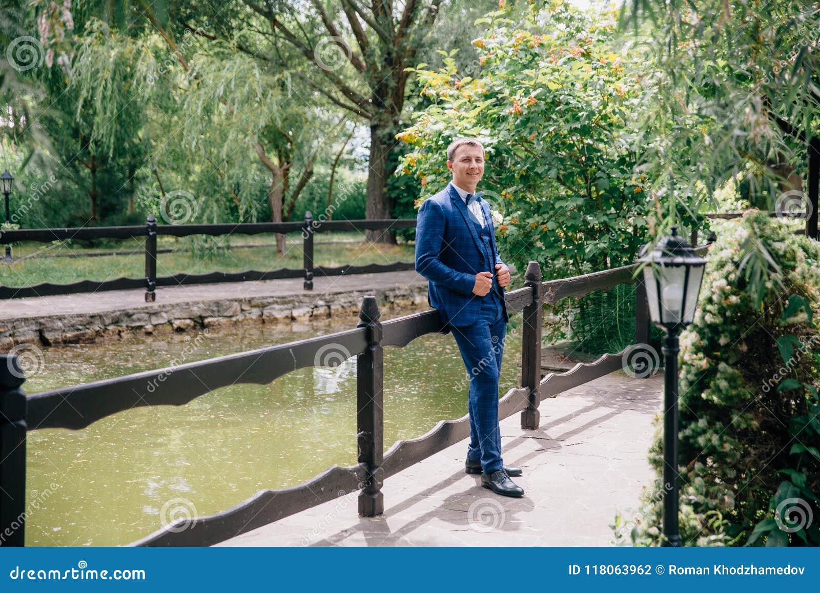 Человек готов и правильно одет для его свадьбы Он гуляет в парке, смотрит пруд и ждет его будущее