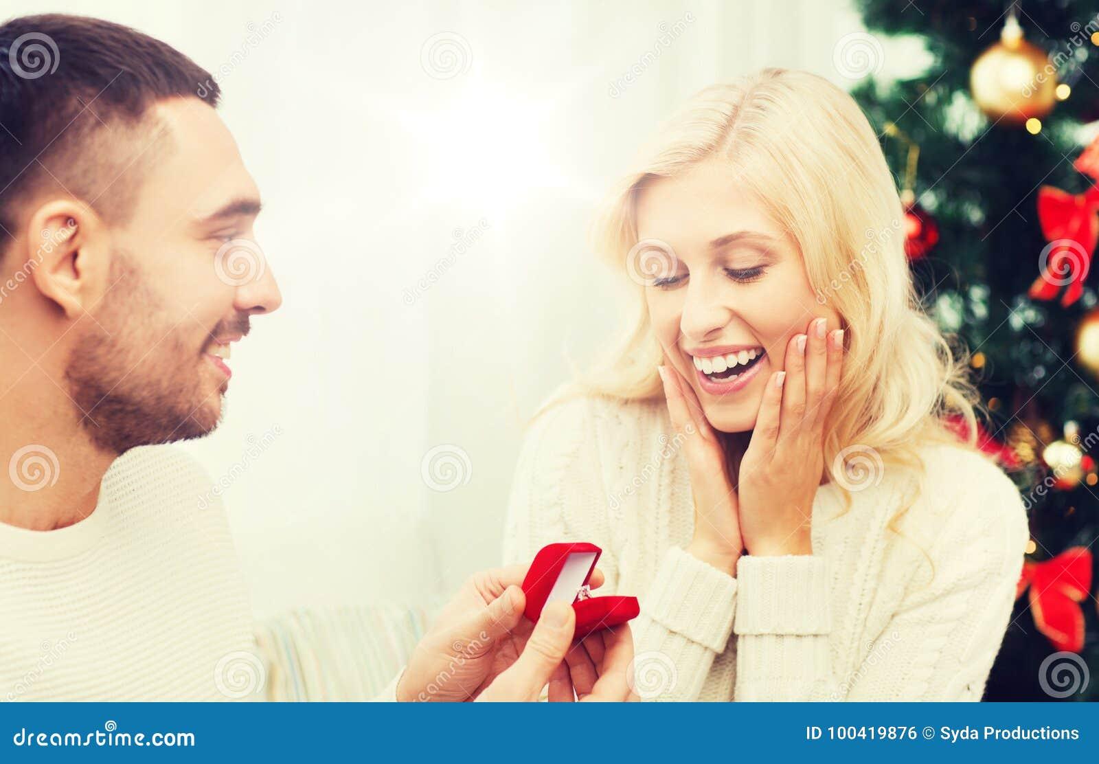 Человек давая обручальное кольцо женщины для рождества