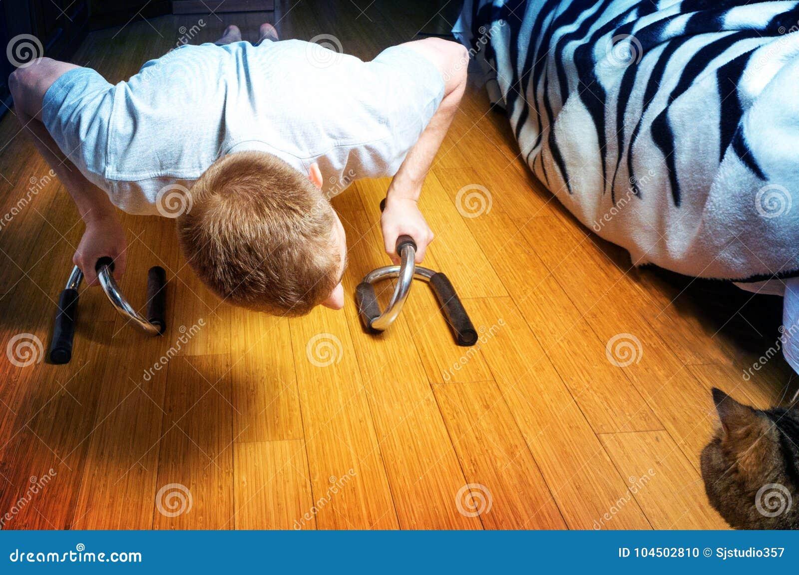 Человек делает нажим-поднимает дома комнату, и вахту кота на ем, здоровом образе жизни