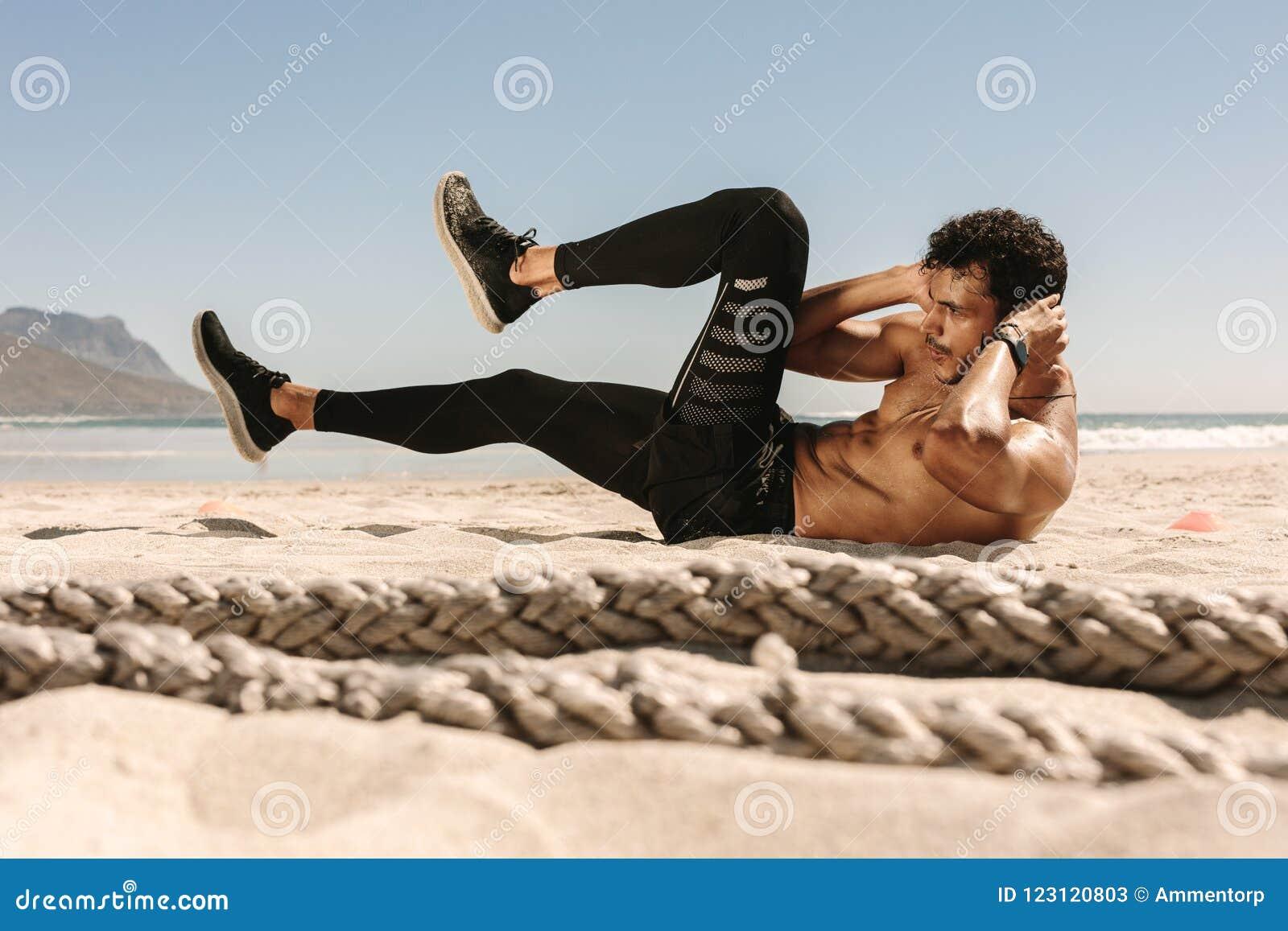 Человек делая разминку брюшка на пляже