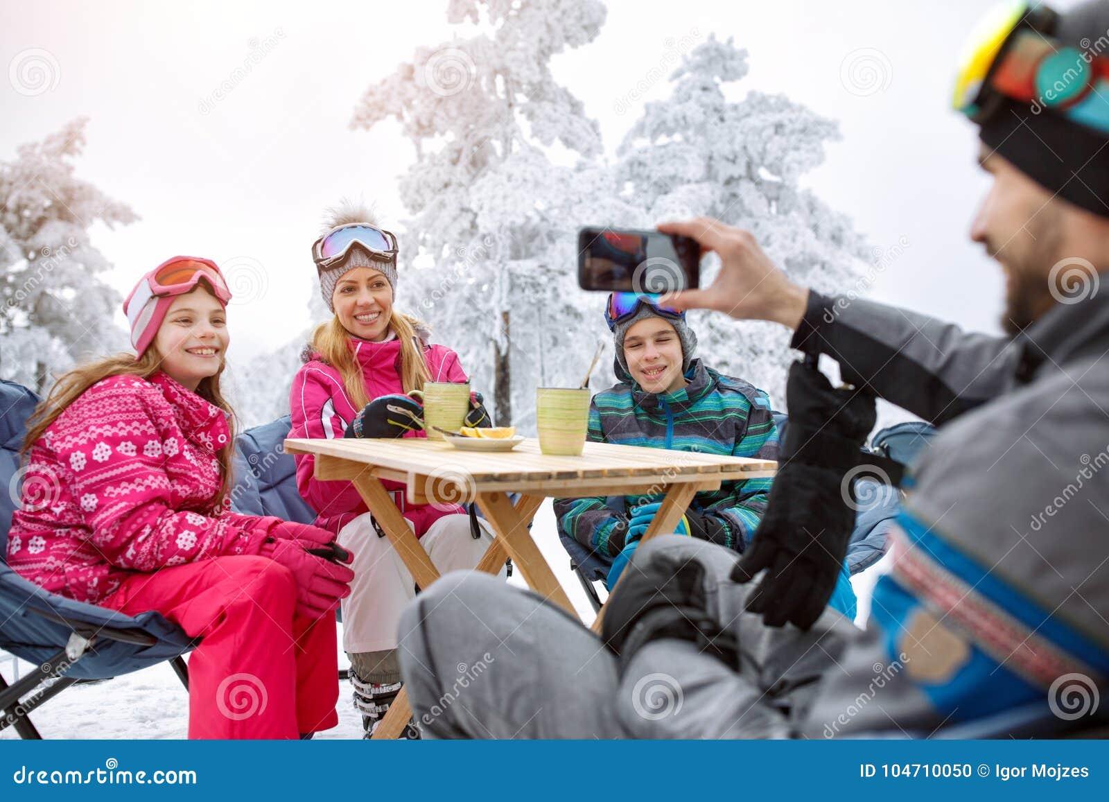 Человек делая семейное фото пока отдыхающ в кафе