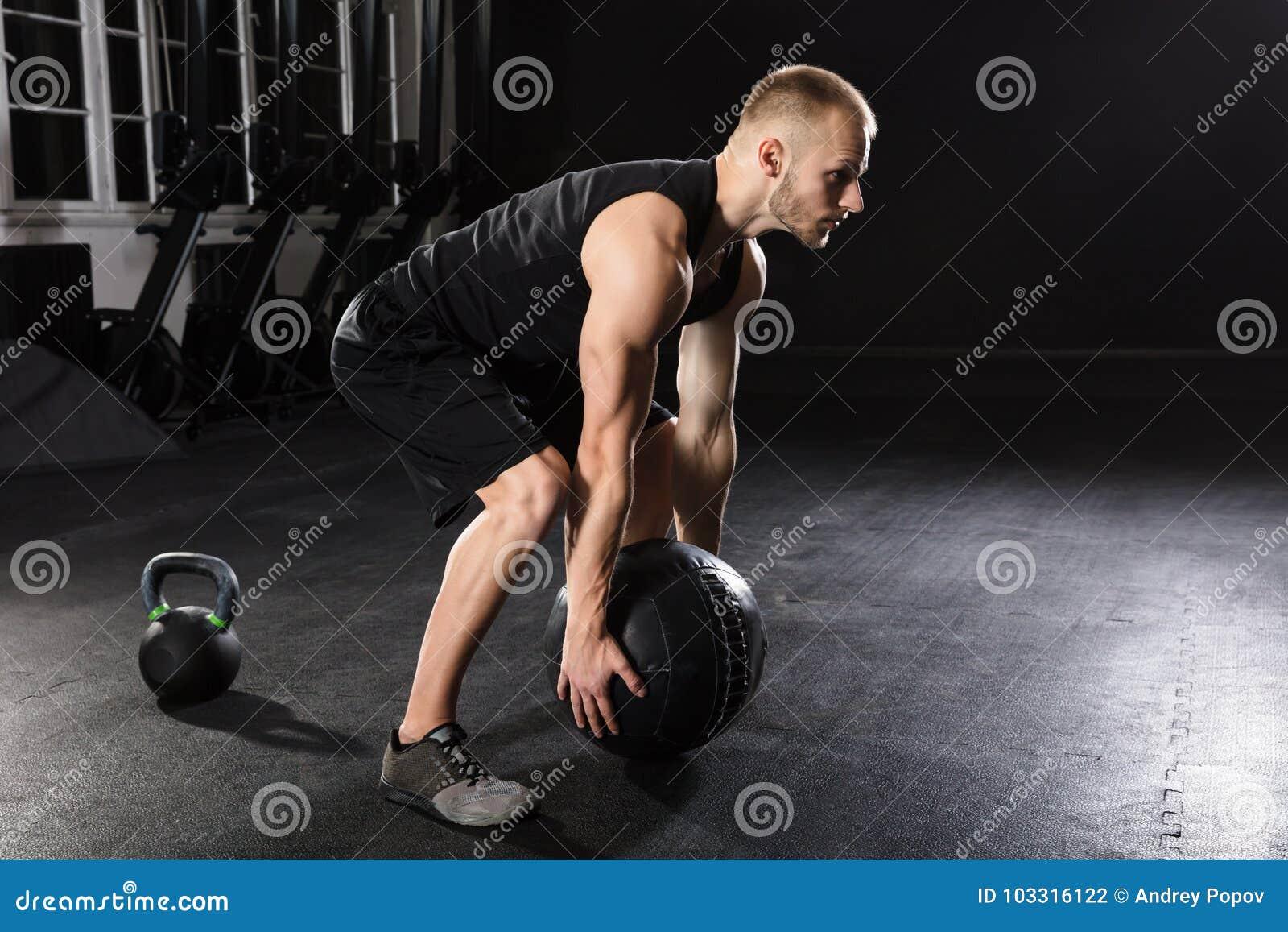 Человек делая тренировку с шариком медицины