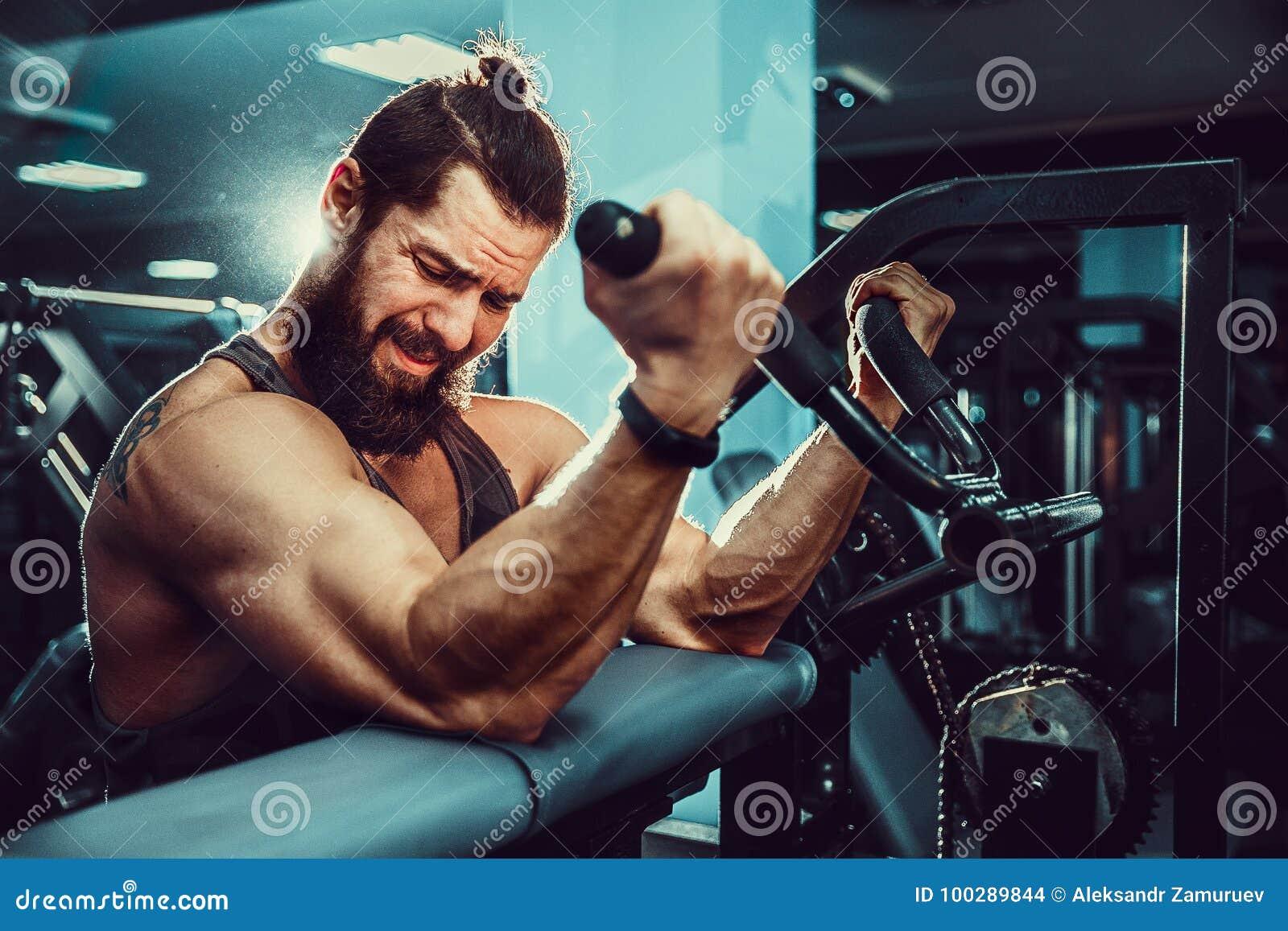 Человек делая тяжеловесную тренировку для бицепса на машине в спортзале
