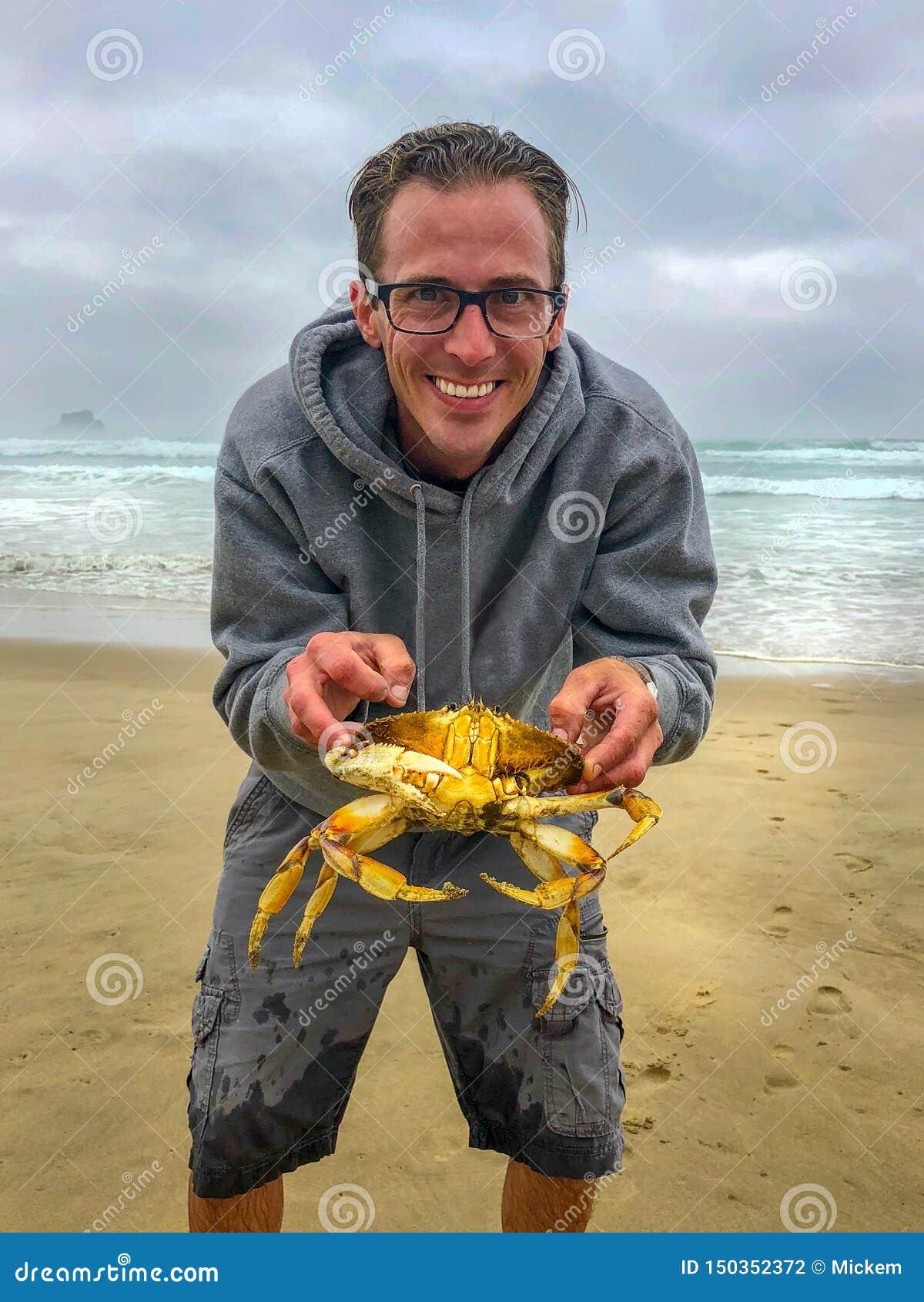 Человек держа большого краба на пляже
