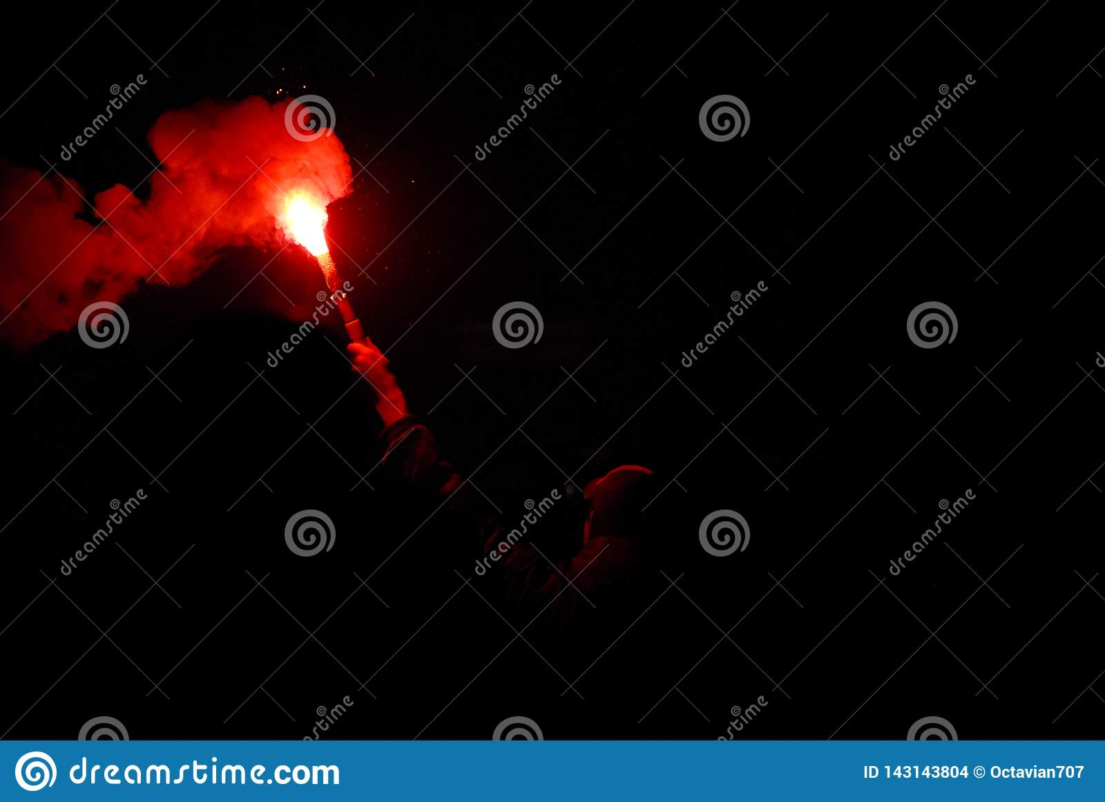 Человек держа горящую красную ручку костра