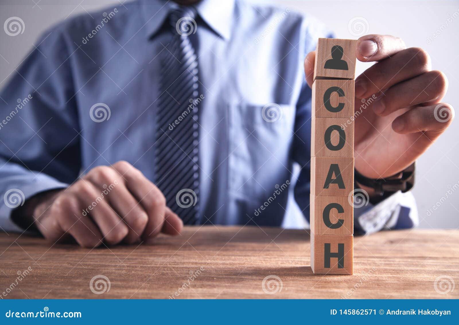 Человек держа деревянный куб со словом тренера r